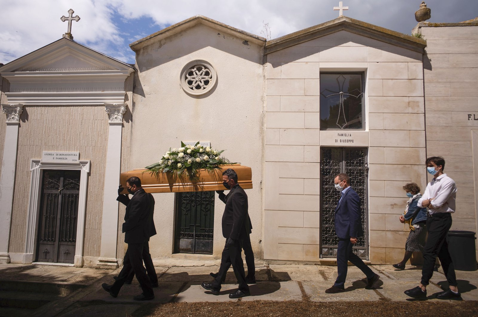 The casket containing the body of Annunziata Ginoble, mother of Sabatino Di Girolamo, mayor of Roseto degli Abruzzi (3rd from R), with his sister Marisa Di Felice (2nd from R) and his son Francesco (R) is taken to her burial site inside the small cemetery of Montepagano, central Italy, at the end of her funeral, May 12, 2020. (AP Photo)