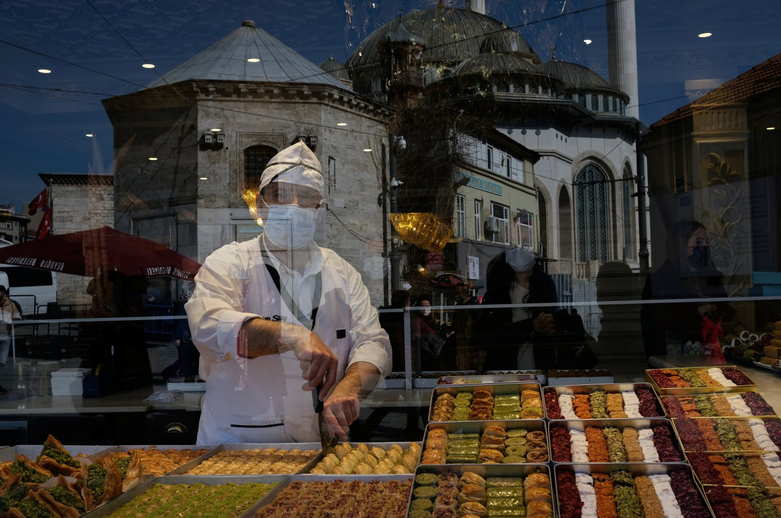 A restaurant employee wearing a protective mask prepares sweets for a customer as the coronavirus disease (COVID-19) outbreak continues, in central Istanbul, Turkey March 4, 2021. (Reuters Photo)