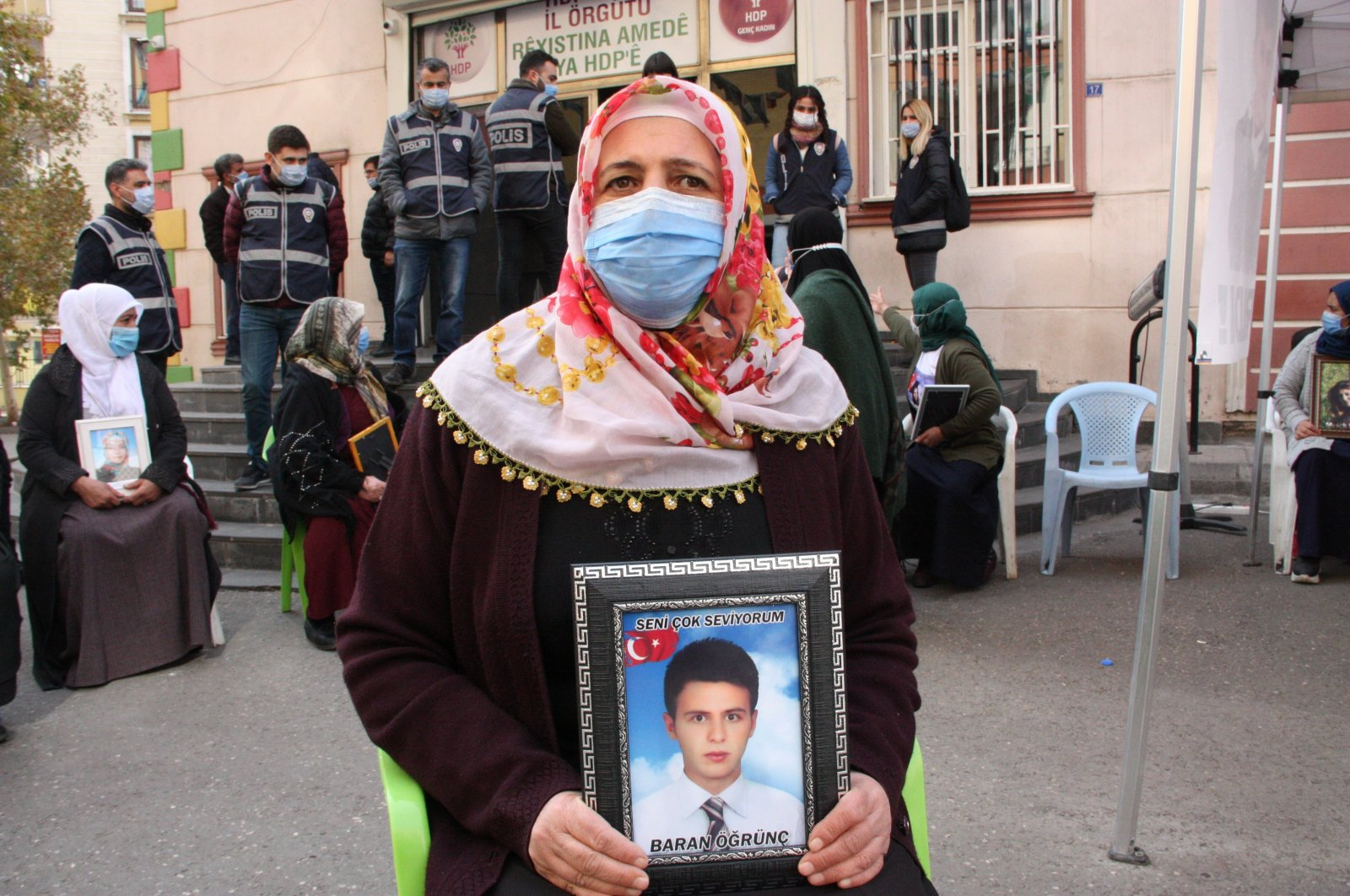 Mother Solmaz Öğrünç poses with a photo of her son Baran, who was abducted by the PKK in 2015 in front of HDP headquarters in Turkey's Diyarbakır province on Dec. 1, 2020 (IHA File Photo)