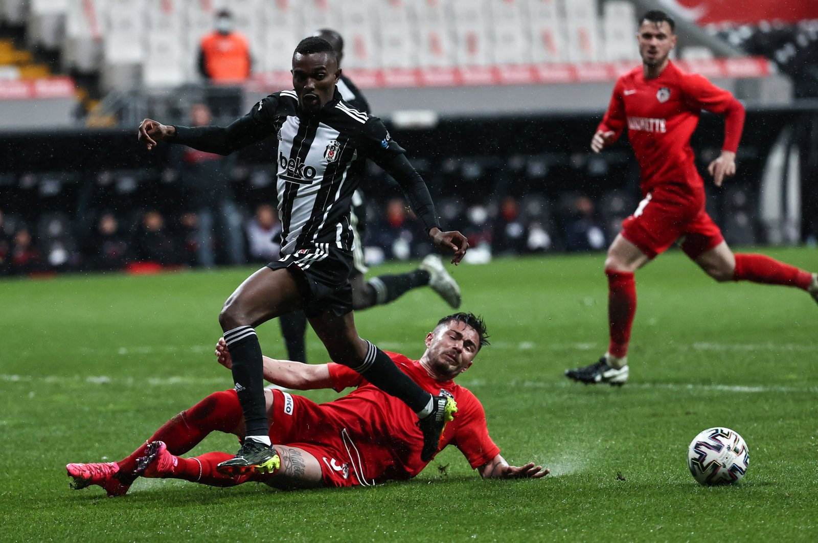 Beşiktaş player Bernard Mensah (running) and Gaziantep player Alin Toşça (on the fllor) at the Turkish Süper Lig game at Vodafone Arena in Istanbul on March 6, 2021 (AA Photo)