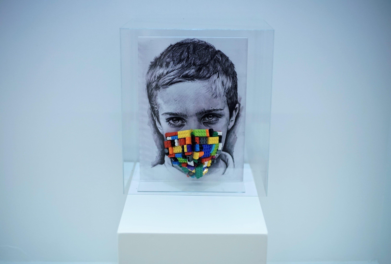 "Simay Bülbül, 'Fanustaki Çocukluk (""Childhood in the Glass Lantern""), lego pieces on textiel, plexi, image, 33 by 24 centimeters."