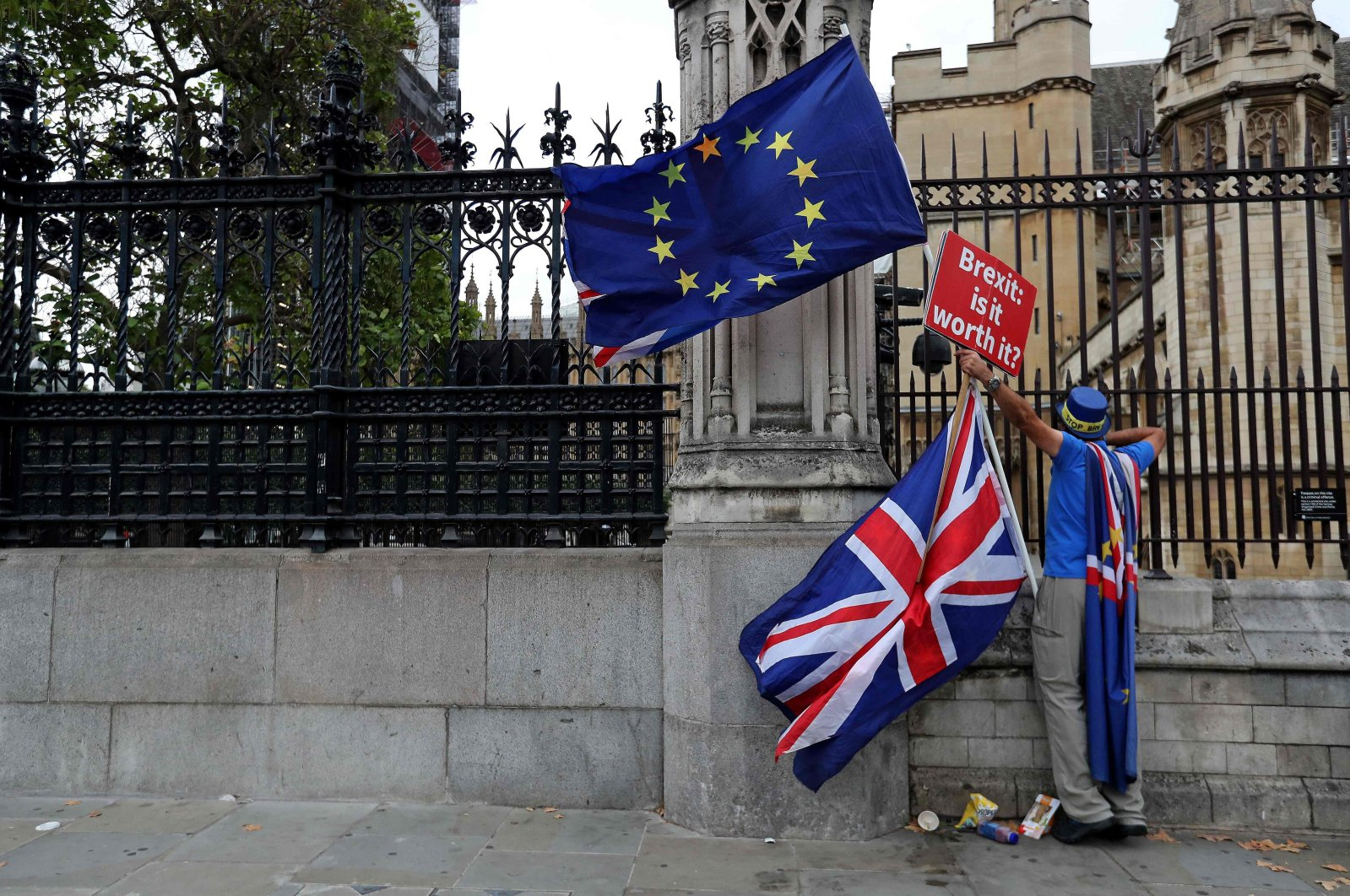 """A demonstrator holds a sign that reads """"Brexit. Is it worth it?"""" while waving the European Union and U.K. flag, England, Sept. 11, 2018. (AFP Photo)"""