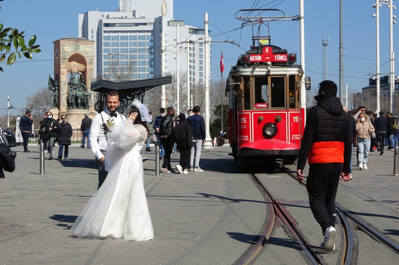 A newlywed couple poses for a photo in Istanbul's famous Taksim Square as people enjoy the first Saturday without a lockdown, March 6, 2021. (IHA Photo)
