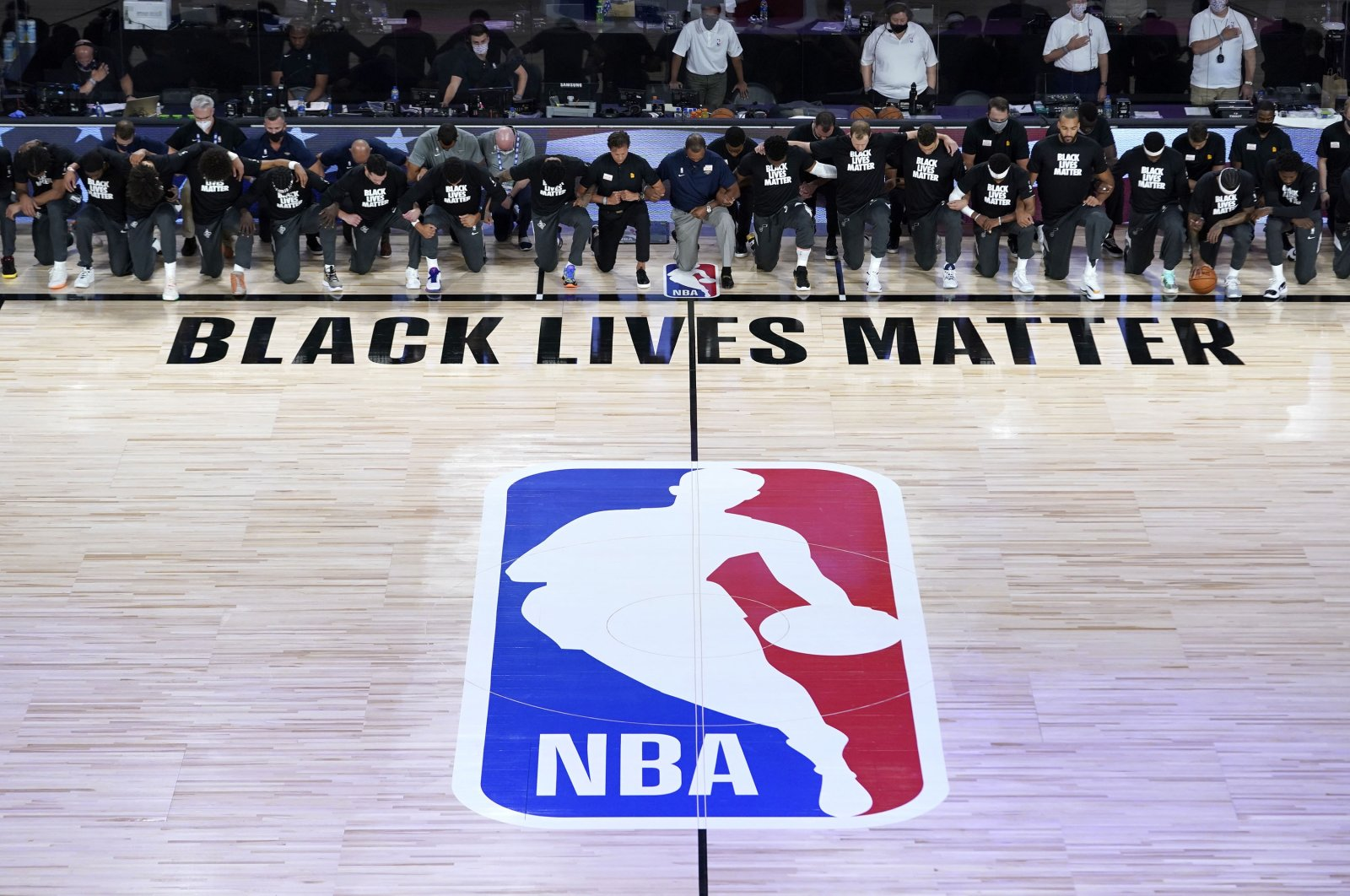 New Orleans Pelicans and Utah Jazz players kneel together around the Black Lives Matter and the NBA logos during the national anthem before the start of a game,Lake Buena Vista, U.S., July 30, 2020. (Reuters Photo)