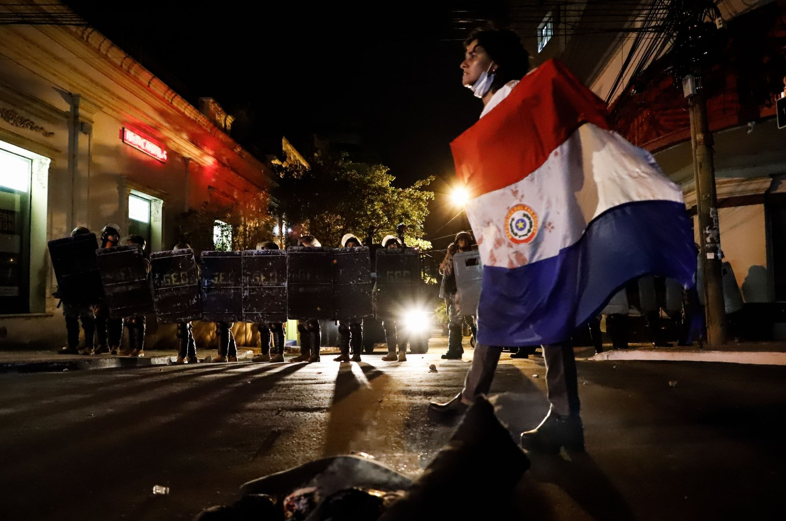 Police officers advance to disperse protesters during a demonstration against the government and President Mario Abdo Benitez for his management of the coronavirus pandemic, in Asuncion, Paraguay, March 5, 2021. (EPA Photo)