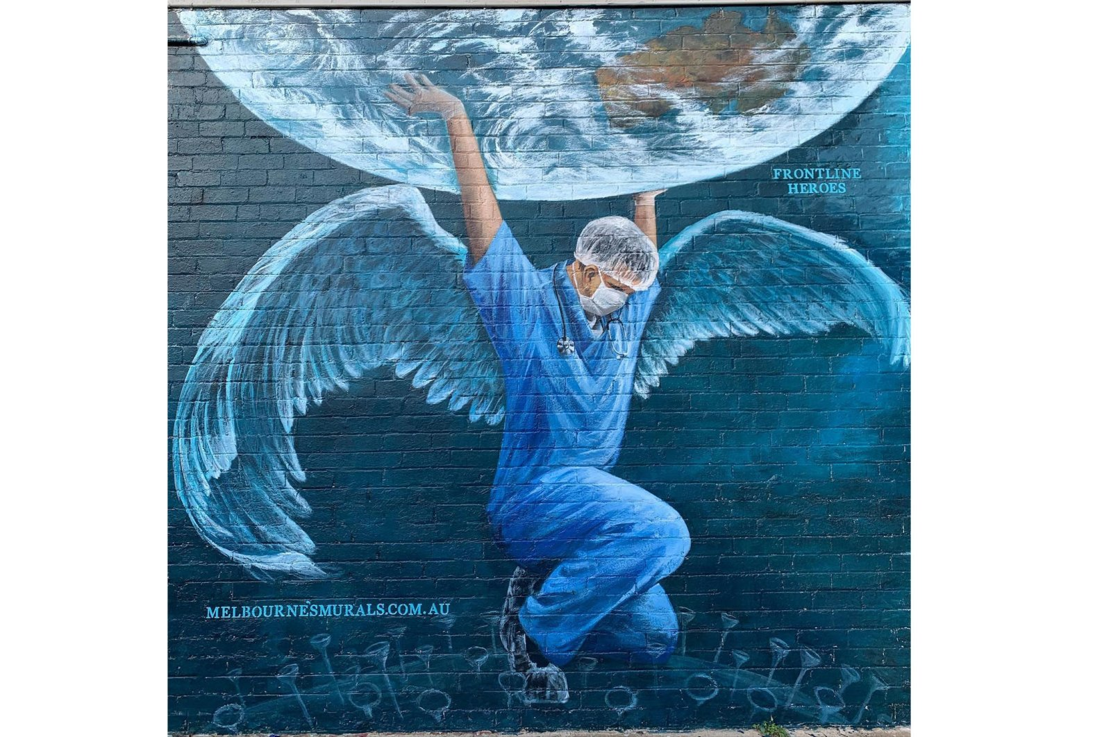 A health care worker in the Atlas pose holding up the earth by Brigitte Dawson and Melissa Turner of Melbourne's Murals, 606 Balcombe Road Blackrock, Melbourne, Victoria, Australia. (Courtesy of YEE)