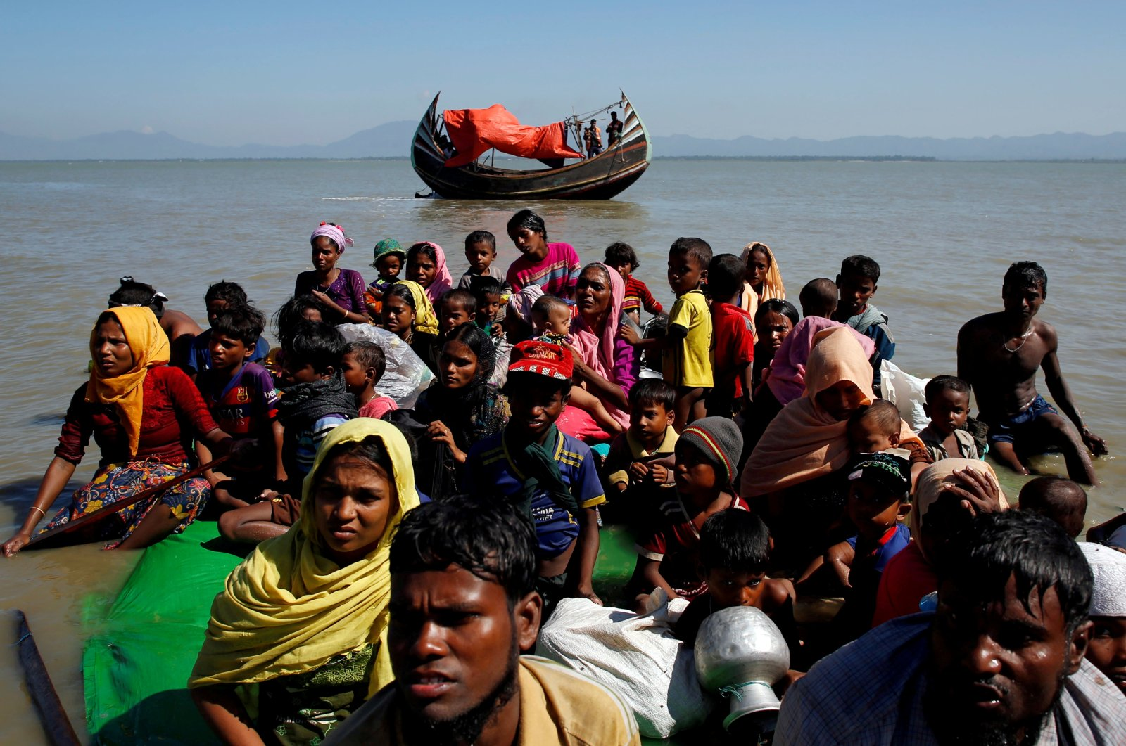 Rohingya refugees sit on a makeshift boat as they get interrogated by the Bangladeshi Border Guard after crossing the Bangladesh-Myanmar border, at Shah Porir Dwip near Cox's Bazar, Bangladesh, Nov. 9, 2017. (Reuters File Photo)