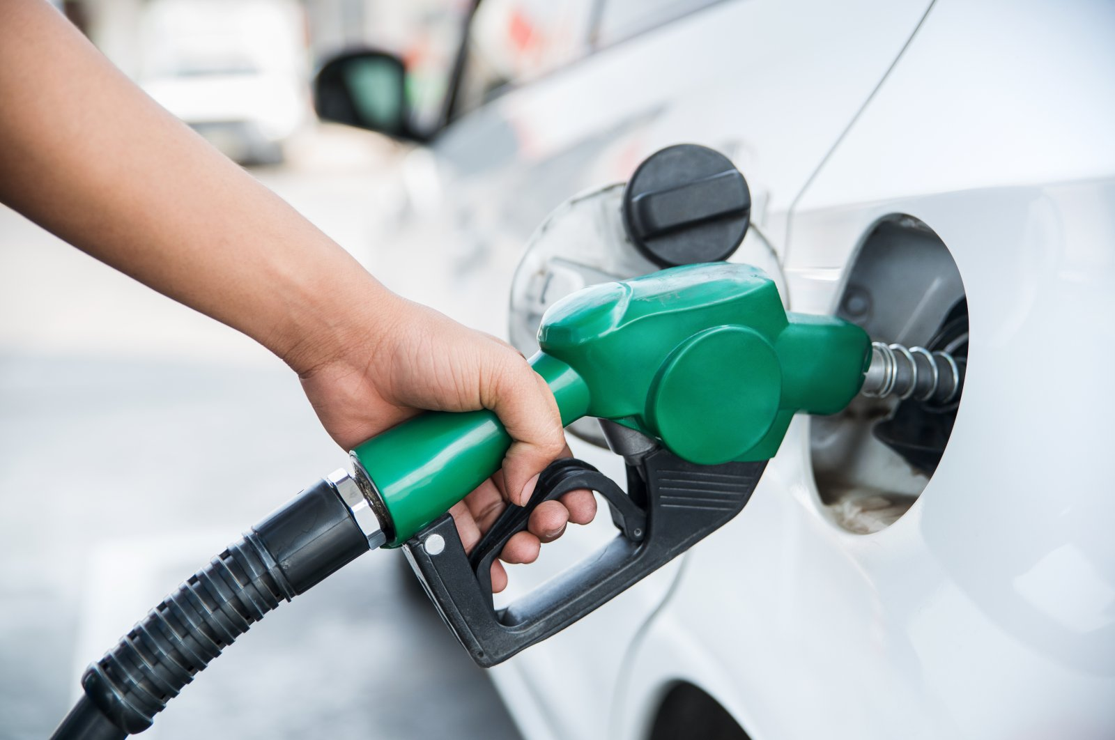A person uses a handle fuel nozzle to refuel. (Shutterstock Photo)