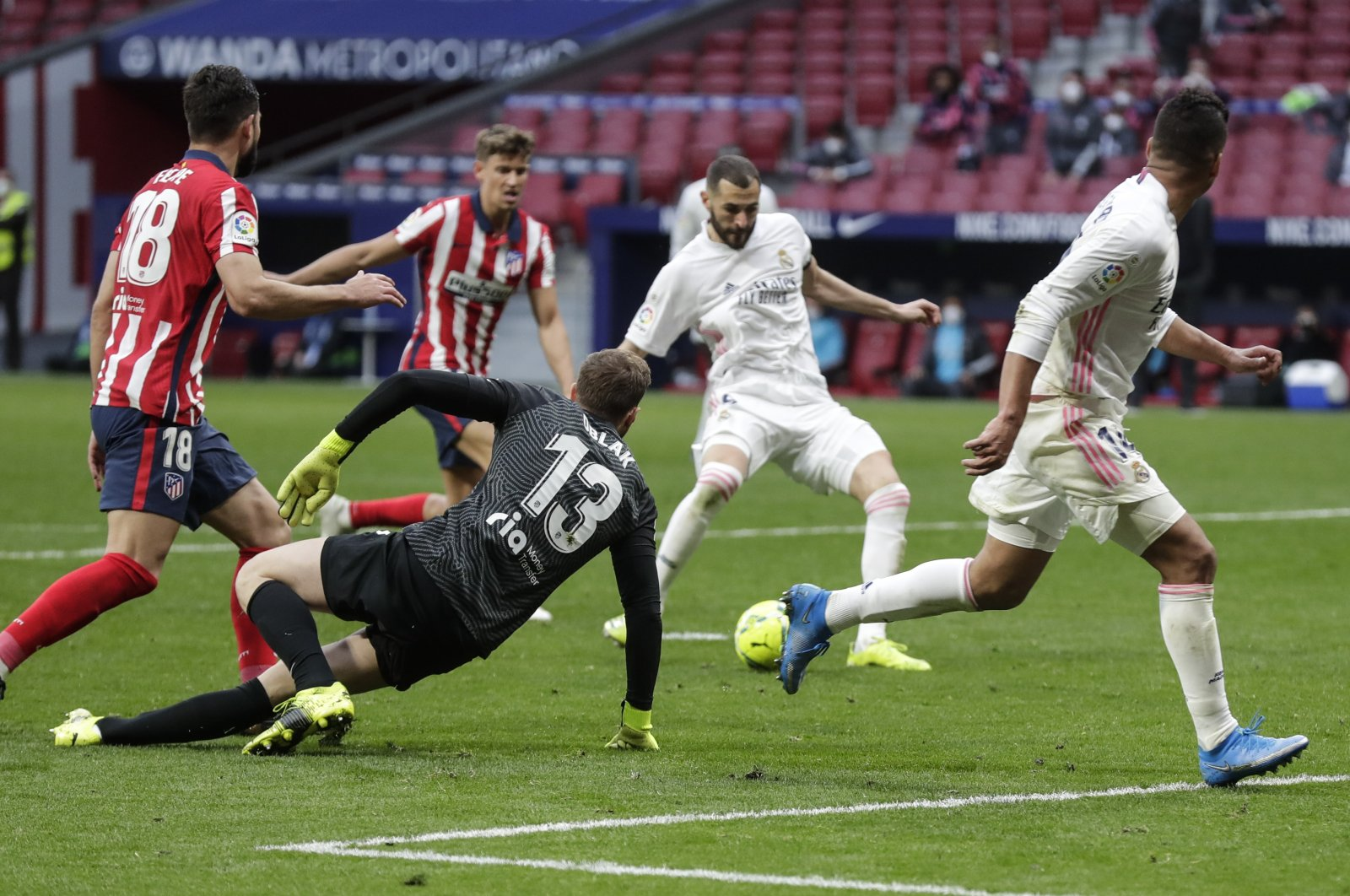 Real Madrid's Karim Benzema scores his side's opening goal during the Spanish La Liga soccer match between Atletico Madrid and Real Madrid at the Wanda Metropolitano stadium in Madrid, Spain, Sunday, March 7, 2021. (AP Photo)