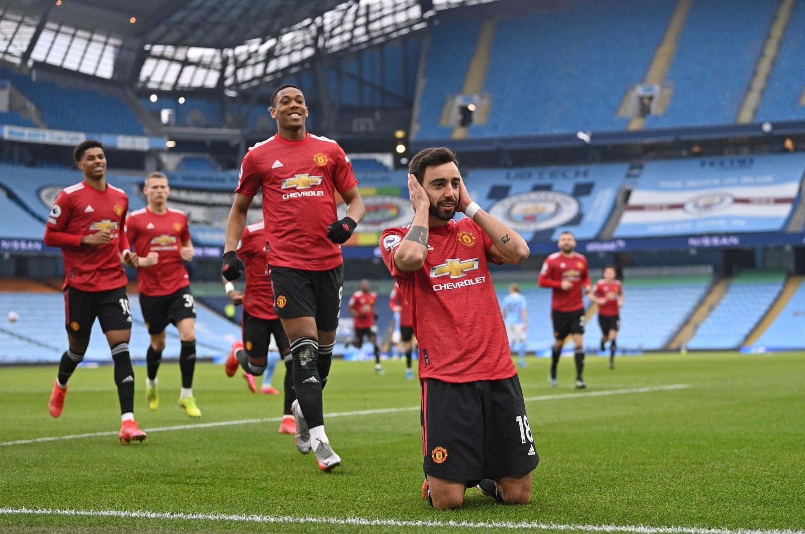 Manchester United's Portuguese midfielder Bruno Fernandes (R) celebrates with teammates after scoring the opening goal from the penalty spot during the English Premier League football match between Manchester City and Manchester United at the Etihad Stadium in Manchester, northwest England, on March 7, 2021. (AFP Photo)