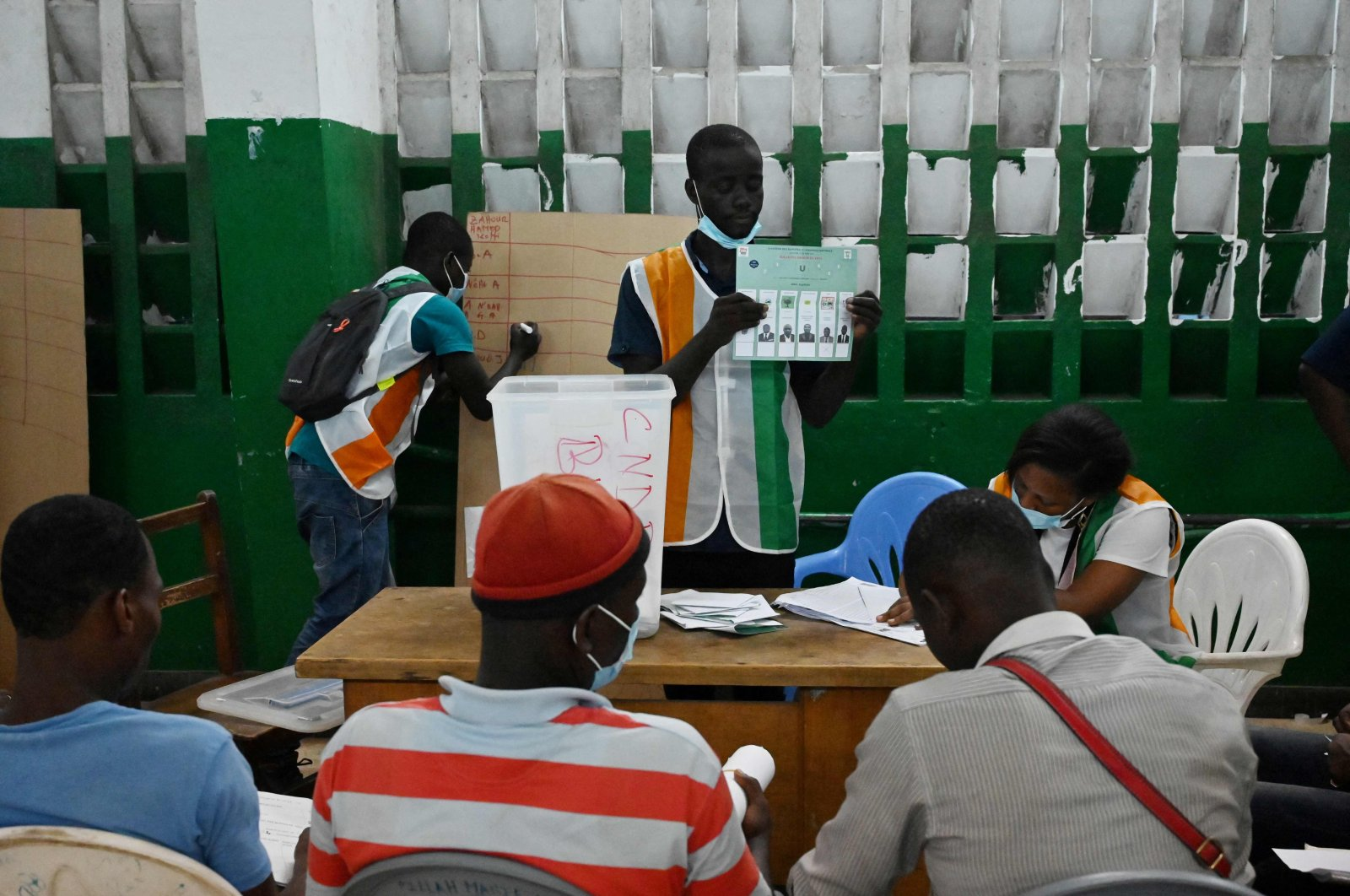 Workers of the Independent Electoral Commission (IEC) count the number of voters after the closure of the polling stations during the legislative elections, in Abidjan, on March 6, 2021. (AFP Photo)