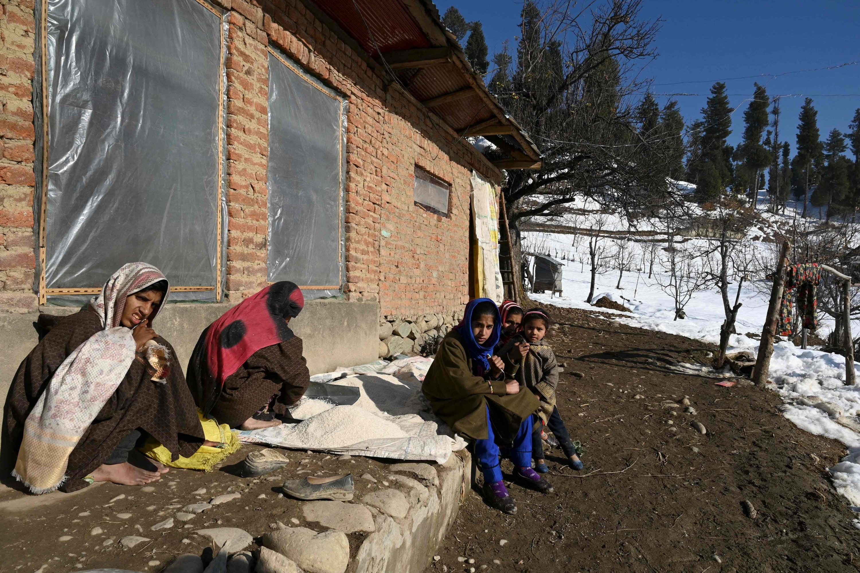 Biya Bano (2nd L) sits with her children outside their mud-brick home in the Nagbal area in Indian-administered Kashmir, Dec. 15, 2020. (AFP Photo)