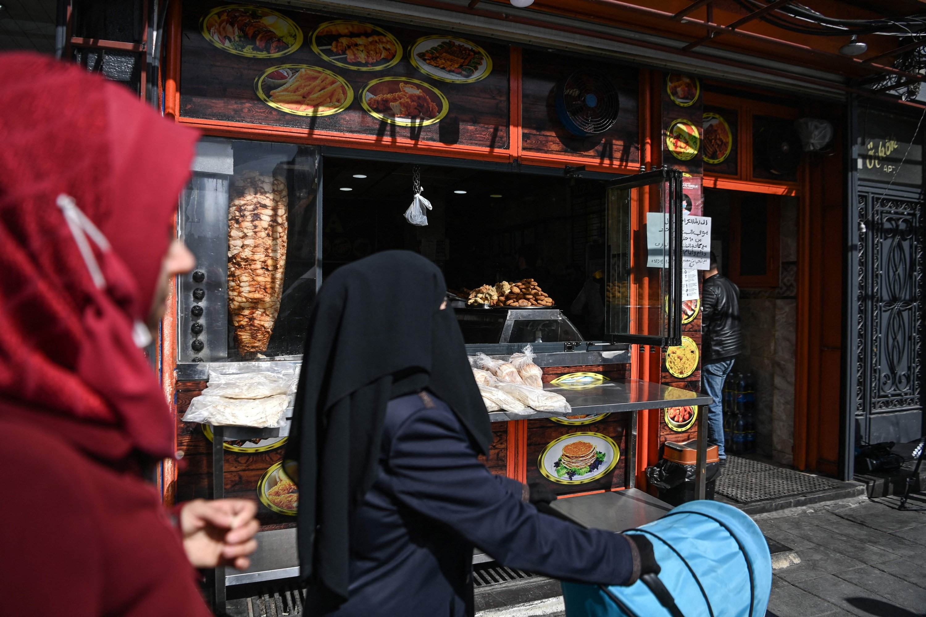 Syrian families pass in front of a Syrian grill shop at Inonu street in Gaziantep, Turkey, Feb. 25, 2021. (AFP)