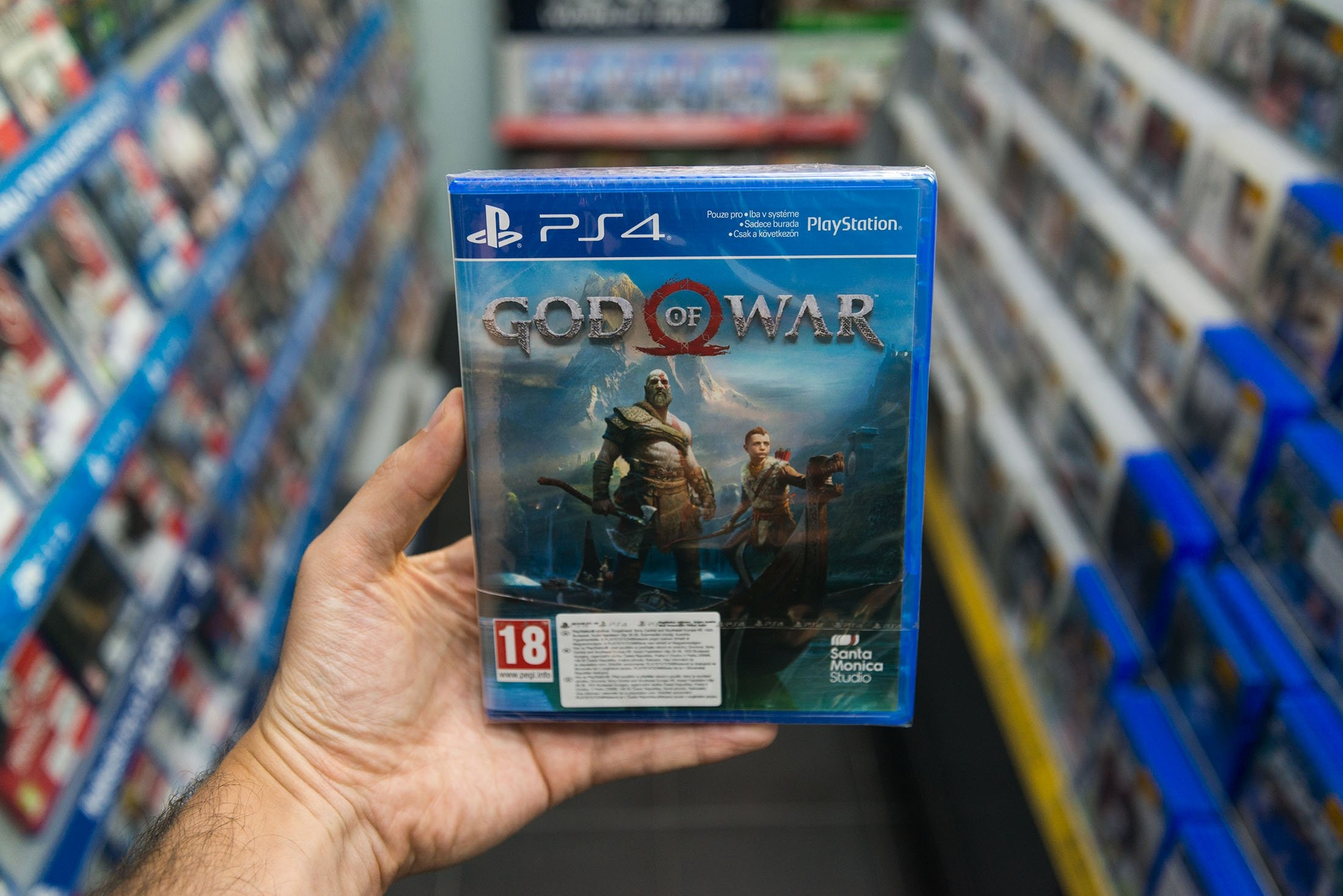 A man holds a God of War videogame for Sony Playstation 4 in a store in Bratislava, Slovakia, May 2018. (Shutterstock Photo)