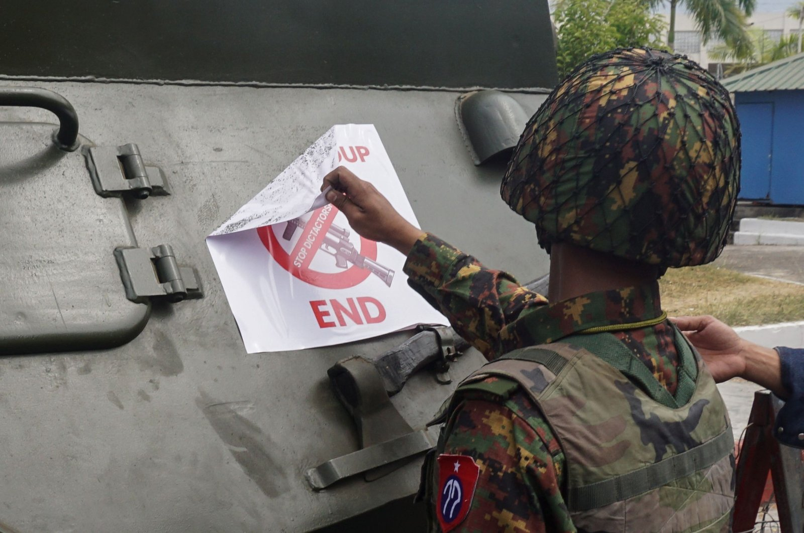 A soldier removes a protest sign denouncing the military coup stuck to an armoured vehicle outside the Central Bank of Myanmar in Yangon on Feb. 15, 2021. (AFP Photo)
