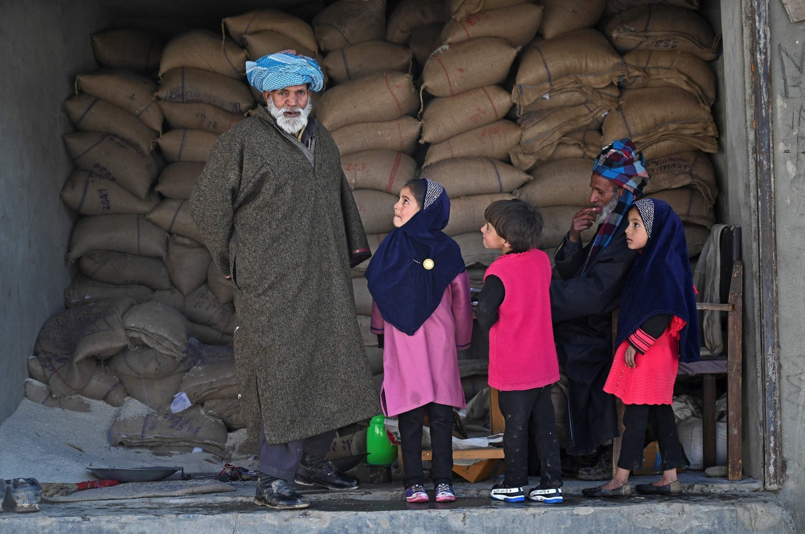 People are seen inside a ration shop where residents have been served notices to provide ownership proof of their houses by the government forest officials in the Nagbal area in Indian-administered Kashmir, Dec. 15, 2020. (AFP Photo)