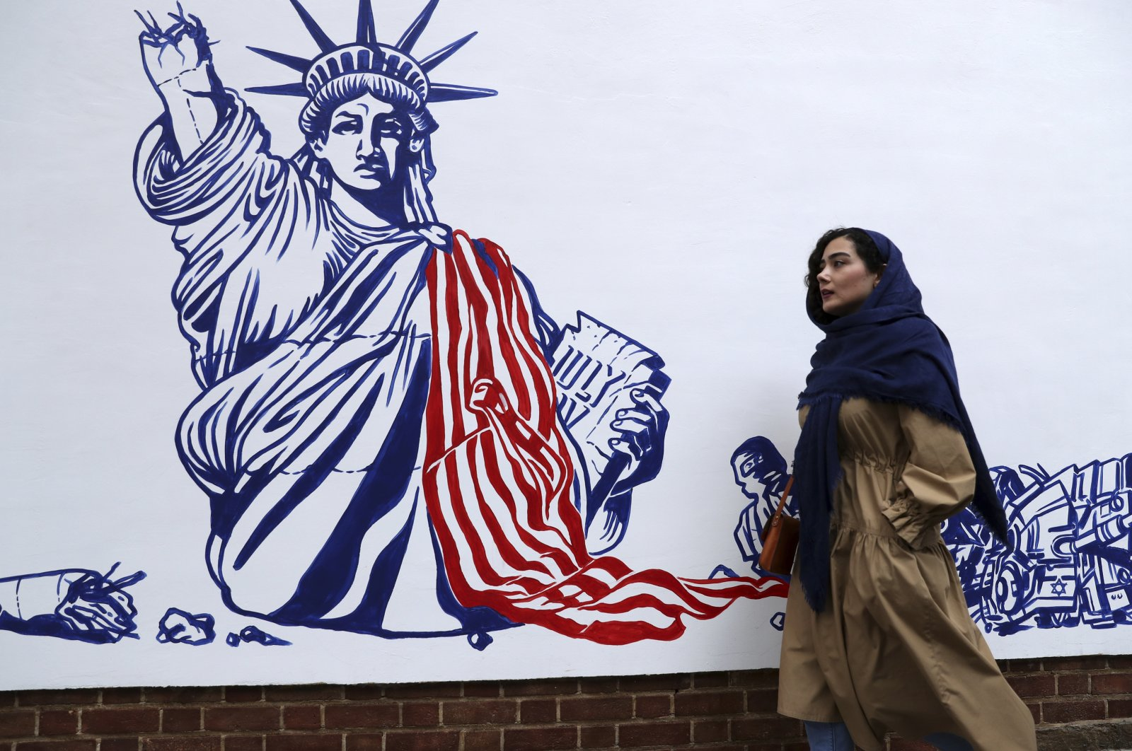 A woman walks past a satirical drawing of the Statue of Liberty on the walls of the former U.S. Embassy unveiled in a ceremony in Tehran, Iran, Nov. 2, 2019. (AP Photo)