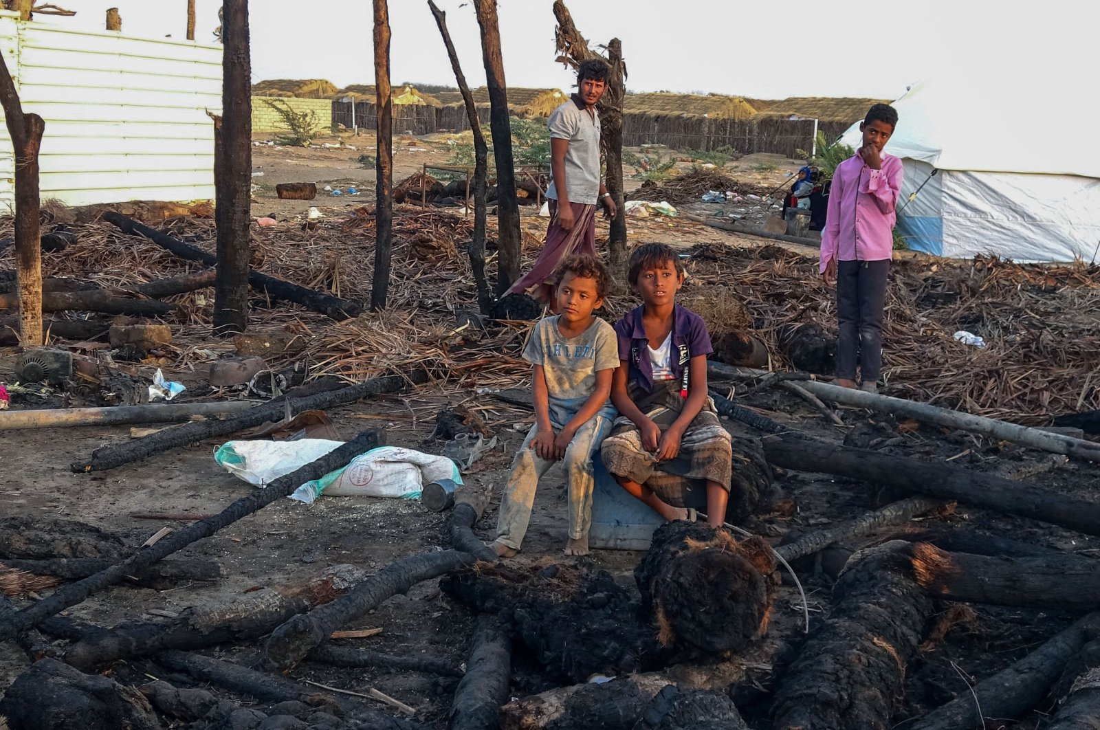 Displaced Yemeni youths sit by calcined wooden poles after a fire broke out in a shelter in the war-ravaged western Hodeida province, on Feb. 16, 2021. (AFP Photo)