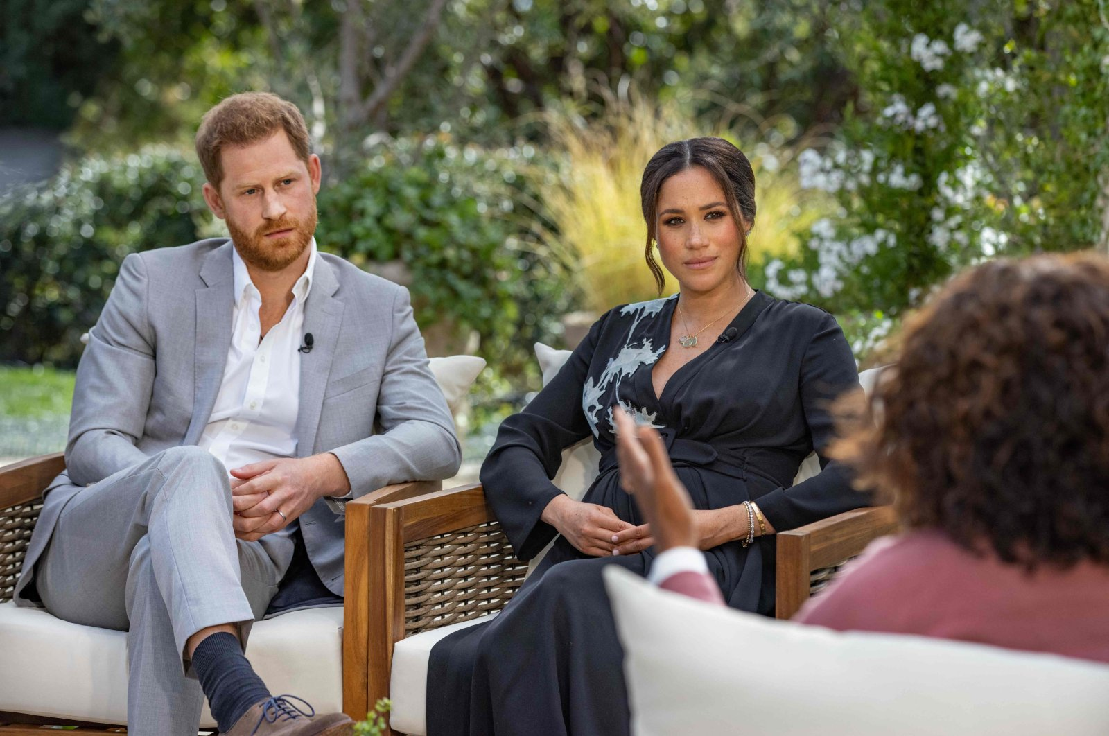 Britain's Prince Harry (L) and his wife Meghan (C), Duchess of Sussex, sit in conversation with U.S. television host Oprah Winfrey, U.S., March 7, 2021. (AFP)