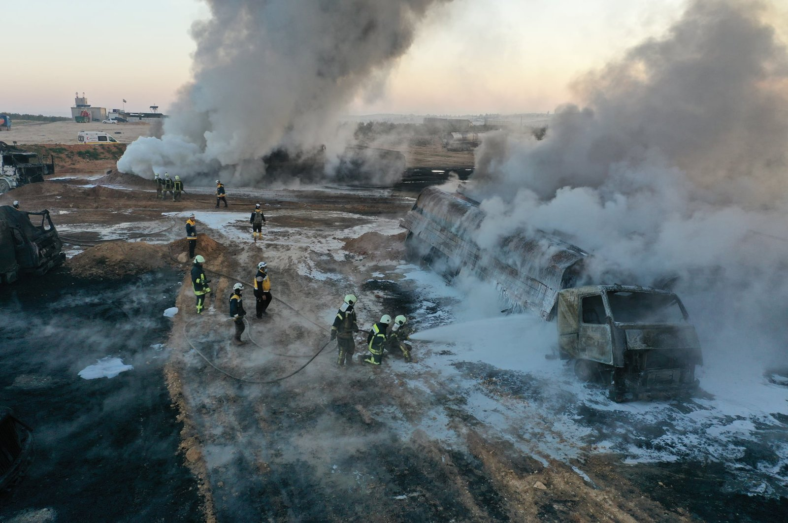 In this photo provided by the Syrian Civil Defense group known as the White Helmets, civil defense workers extinguish burning oil tanker trucks after a suspected missile strike around the towns of Jarablus and al-Bab, near the border with Turkey, in western Aleppo province, Syria, March 6, 2021. (AP Photo)