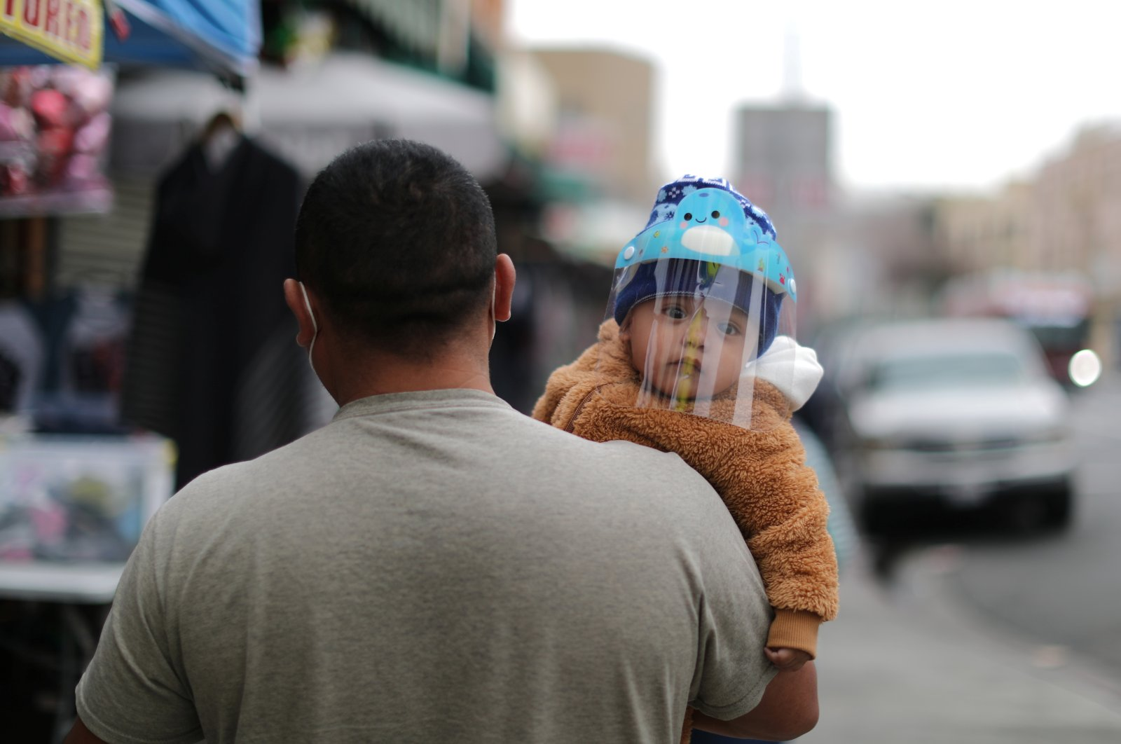 A man carries a baby wearing a face shield as protection against the coronavirus, in Los Angeles, California, U.S., Feb. 10, 2021. (REUTERS Photo)