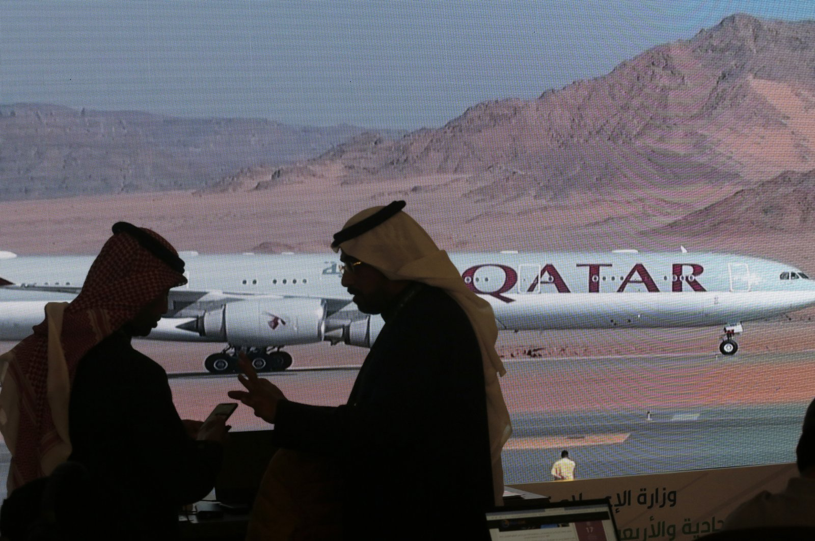 Journalists chat as a video of a plane carrying the Qatari delegation while landing at at Al-Ula airport is shown on a screen, where the 41st Gulf Cooperation Council (GCC) meeting takes place, Saudi Arabia, Jan. 5, 2021. (AP Photo)
