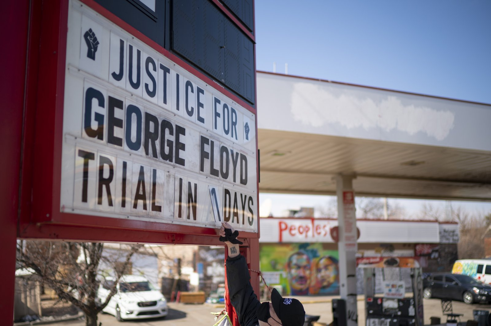 """Billy Briggs, who lives just 170 steps from where George Floyd was killed, on Sunday updates a countdown sign to """"1"""" which he maintains at the gas station on the corner of George Floyd Square in Minneapolis, March 8, 2021. (AP)"""