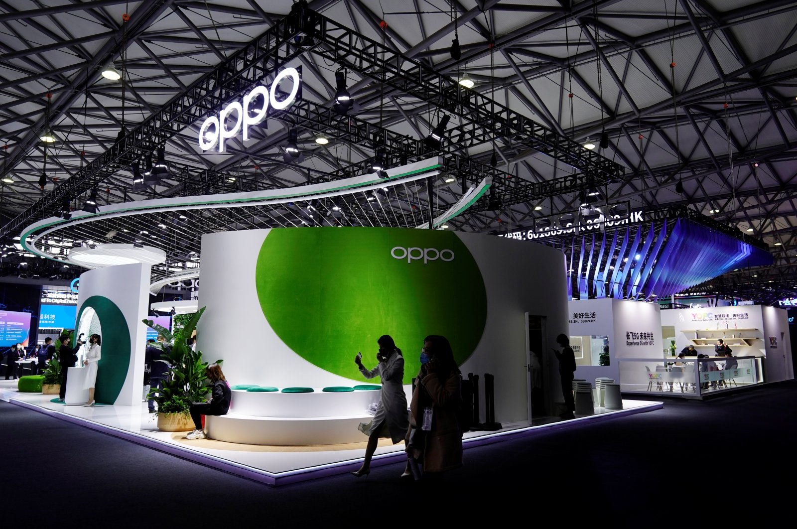 People walk past a booth of smartphone maker Oppo at the Mobile World Congress (MWC) in Shanghai, China, Feb. 23, 2021. (Reuters Photo)