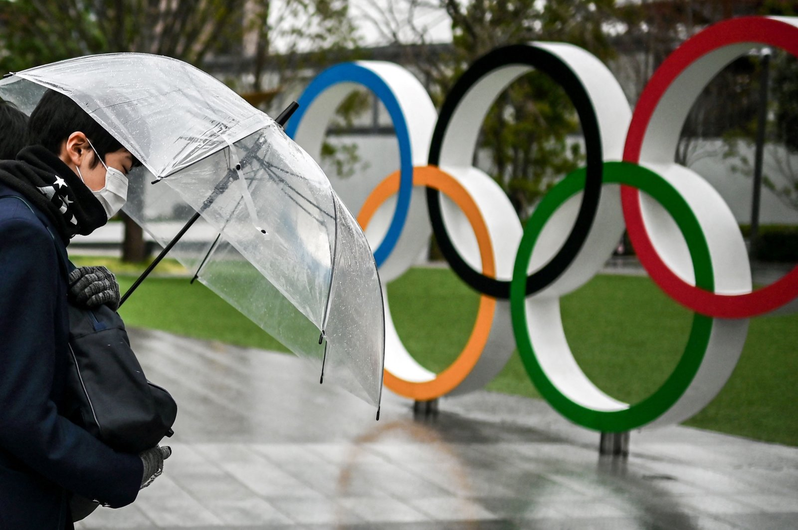 A man walking past the Olympic rings outside the Olympic Museum in Tokyo, Japan, Jan. 28, 2021. (AFP Photo)