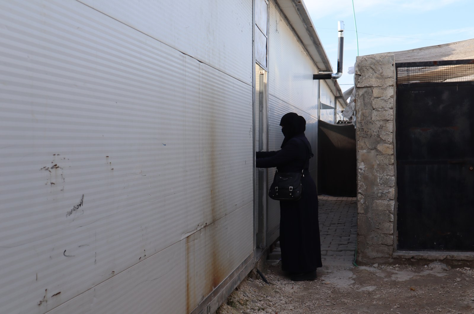 Muna Abban, a Syrian woman who fled the Bashar Assad regime's attacks in Aleppo, is seen in in front of her container house in Syria's Azaz, March 7, 2021 (AA Photo)