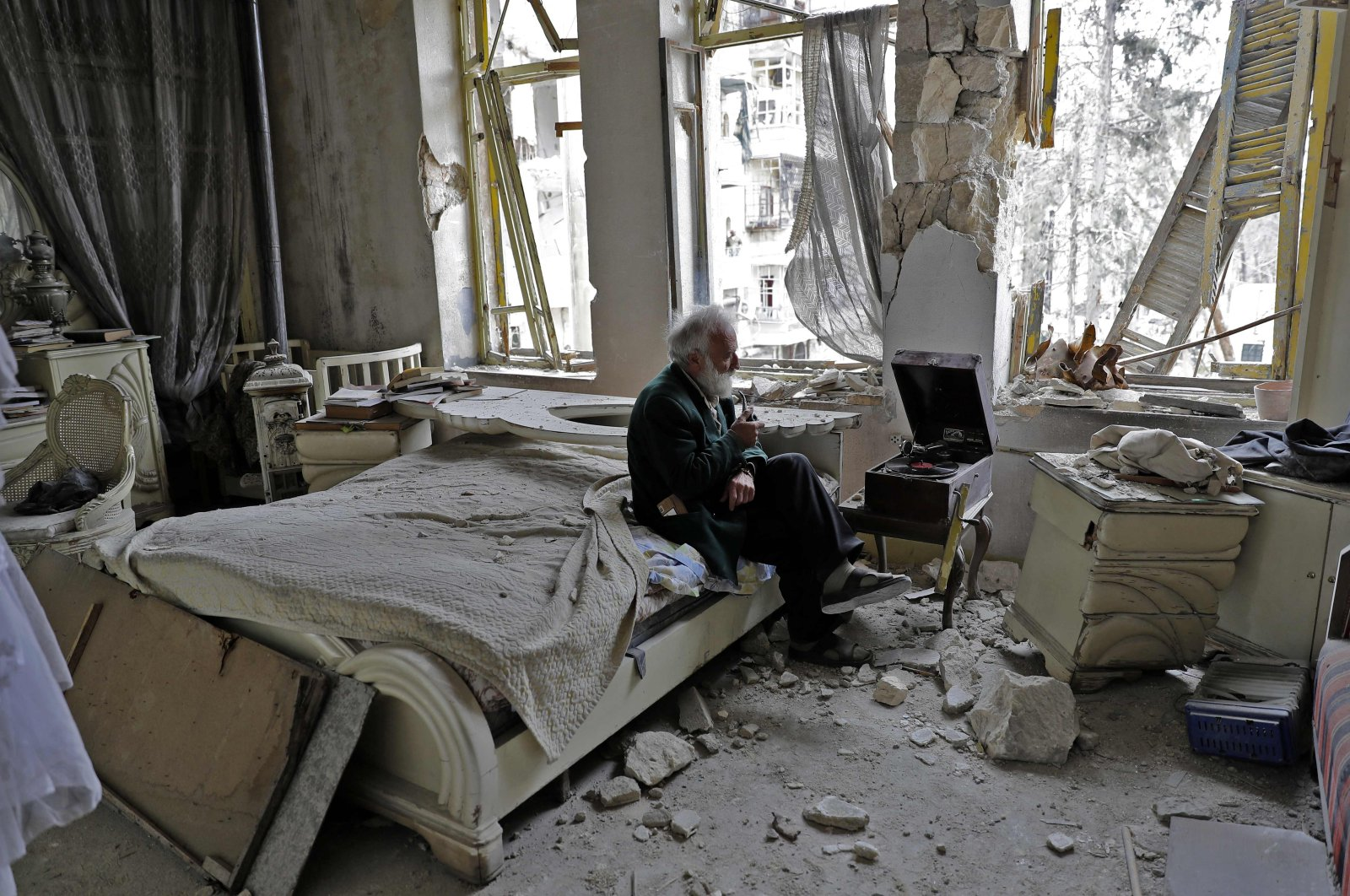 In this file photo, Mohammed Mohiedin Anis, 70, smokes his pipe as he sits in his destroyed bedroom listening to music on his gramophone in Aleppo's formerly opposition-held al-Shaar neighborhood, Syria, March 9, 2017. (AFP Photo)