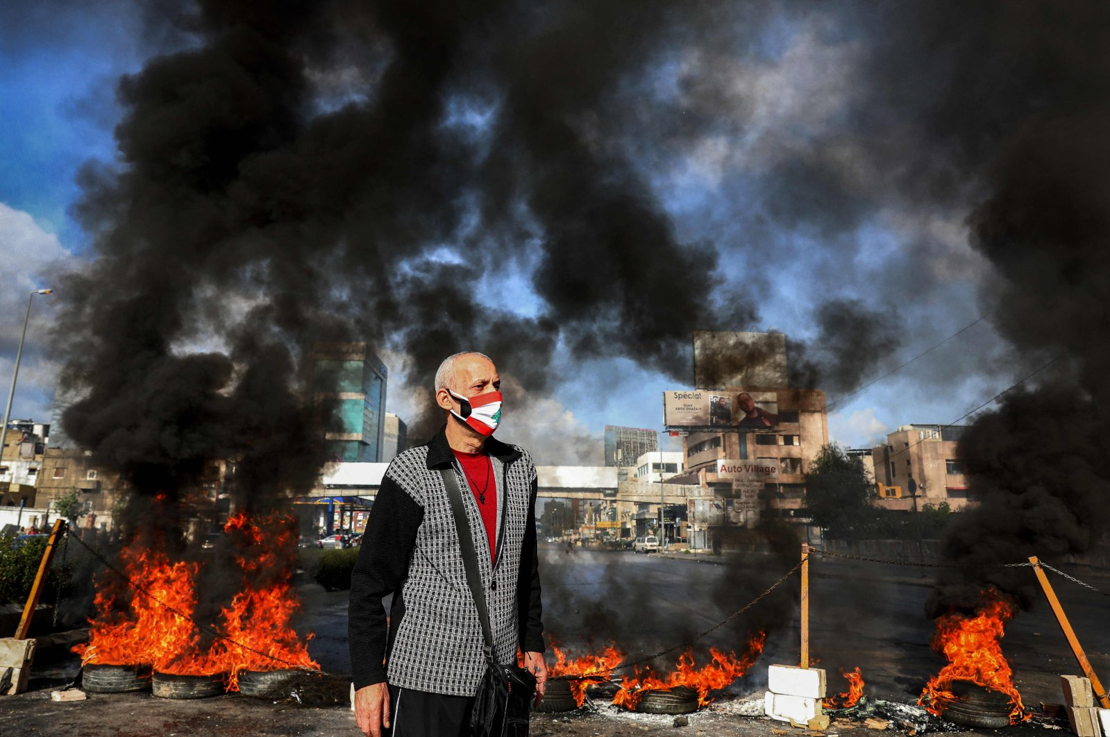 A man clad in a mask depicting the Lebanese flag stands next to flaming tires at a makeshift roadblock set up by anti-government demonstrators in the area of Dora on the northern outskirts of Lebanon's capital Beirut on March 8, 2021. (AFP Photo)