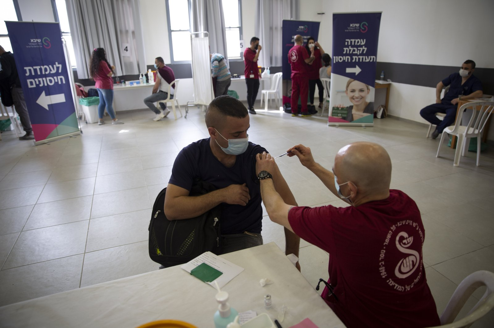 A Palestinian laborer who works in Israel receives his first dose of the Moderna COVID-19 vaccine at a coronavirus vaccination center set up at the Taiba checkpoint crossing between Israel and the West Bank, near the West Bank town of Tulkarem, Monday, March 8, 2021. (AP Photo)