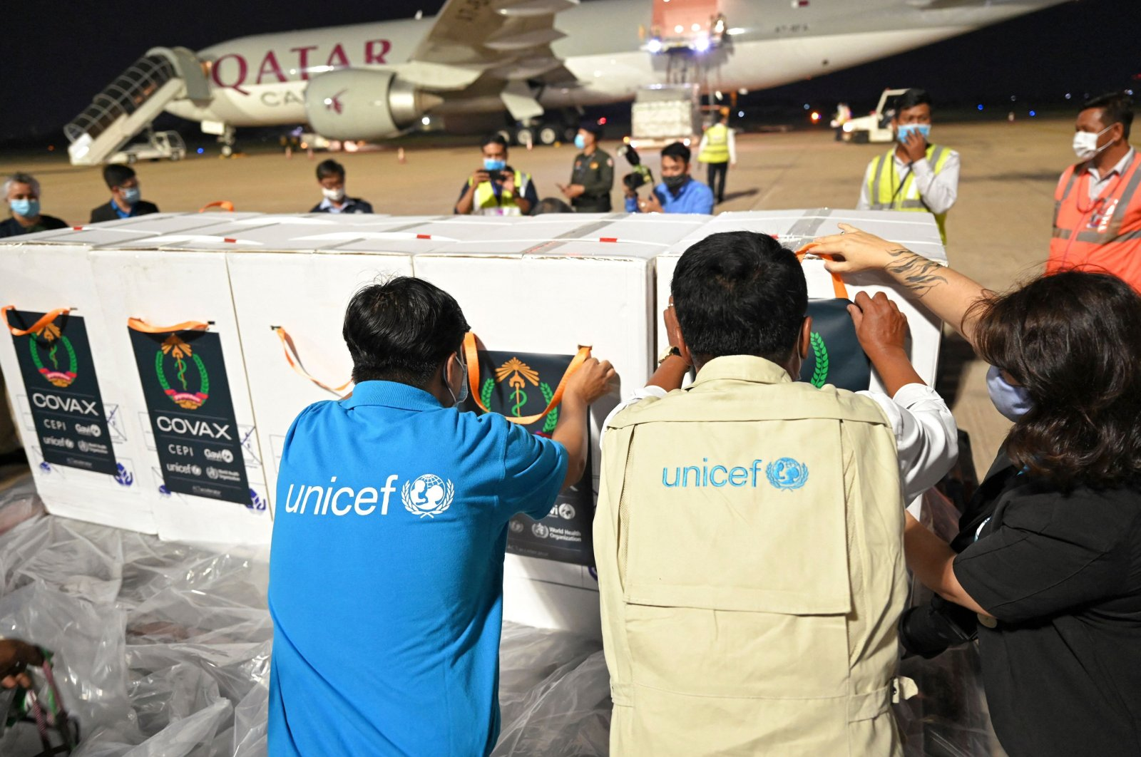 UNICEF staff place stickers on boxes of COVID-19 vaccines during the handover ceremony of the first allocation of Indian-made AstraZeneca vaccine from the Covax facility, at Phnom Penh International Airport on March 2, 2021. (AFP Photo)
