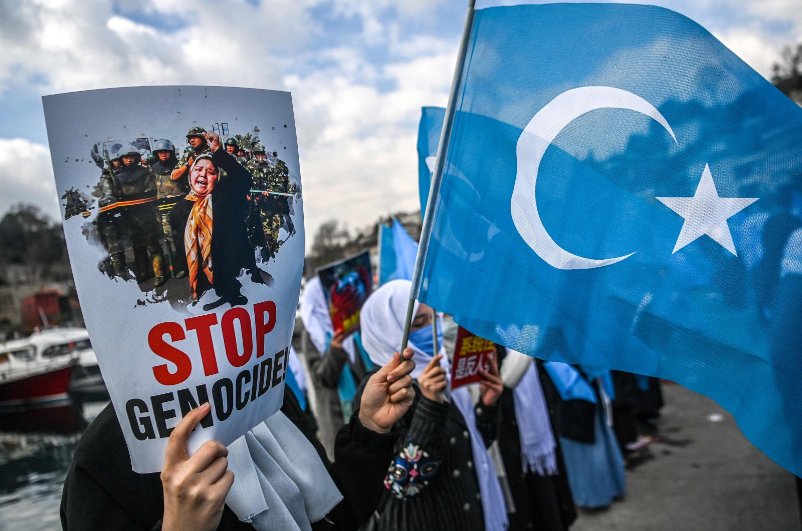 Muslim Uyghur women hold placards and East Turkestan flags as they demonstrate outside the consulate in Istanbul on Women's Day, demanding news of their relatives near China. Istanbul, Turkey, March 8, 2021 (AFP)