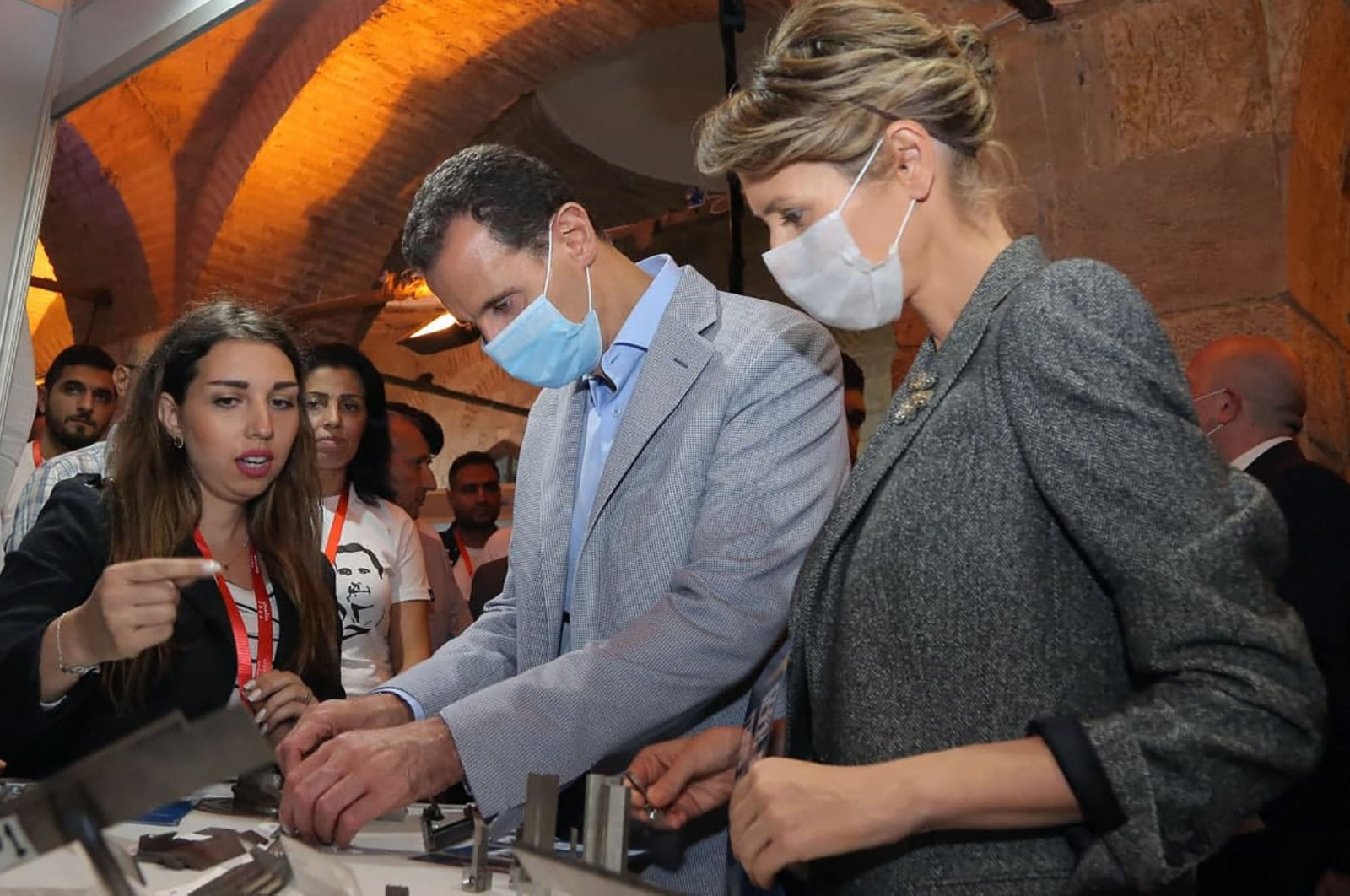 A file handout picture released by the official Syrian Arab News Agency (SANA) on November 4, 2020 shows Bashar Assad and his wife Asma, wearing face masks due to the COVID-19 pandemic, during a visit to a state-sponsored fair in Damascus for small businesses from Aleppo, northern Syria. (Photo: SANA via AFP)
