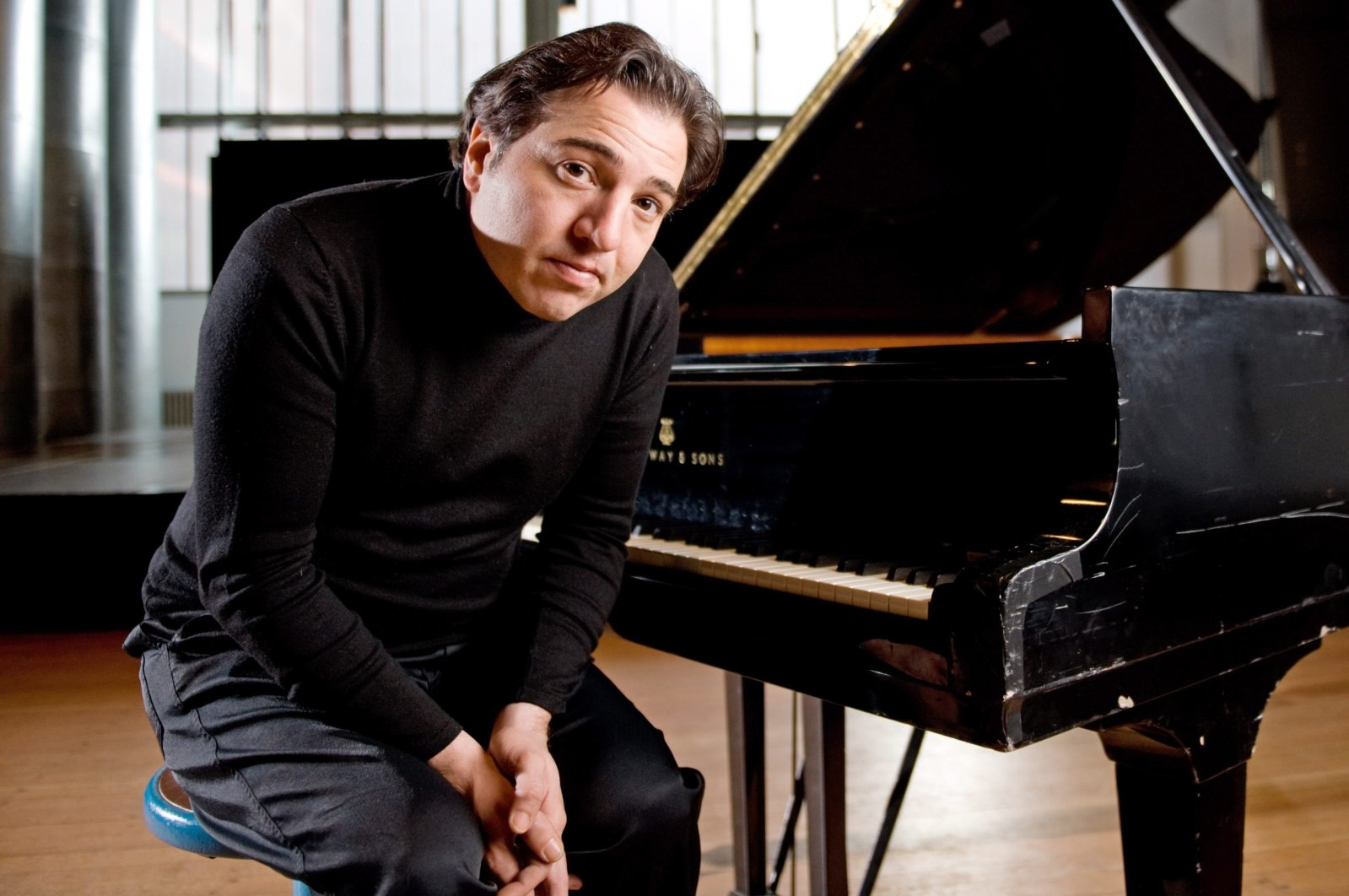 Turkish pianist Fazil Say poses in front of a piano, Essen, Germany, Feb. 3, 2010 (AFP)