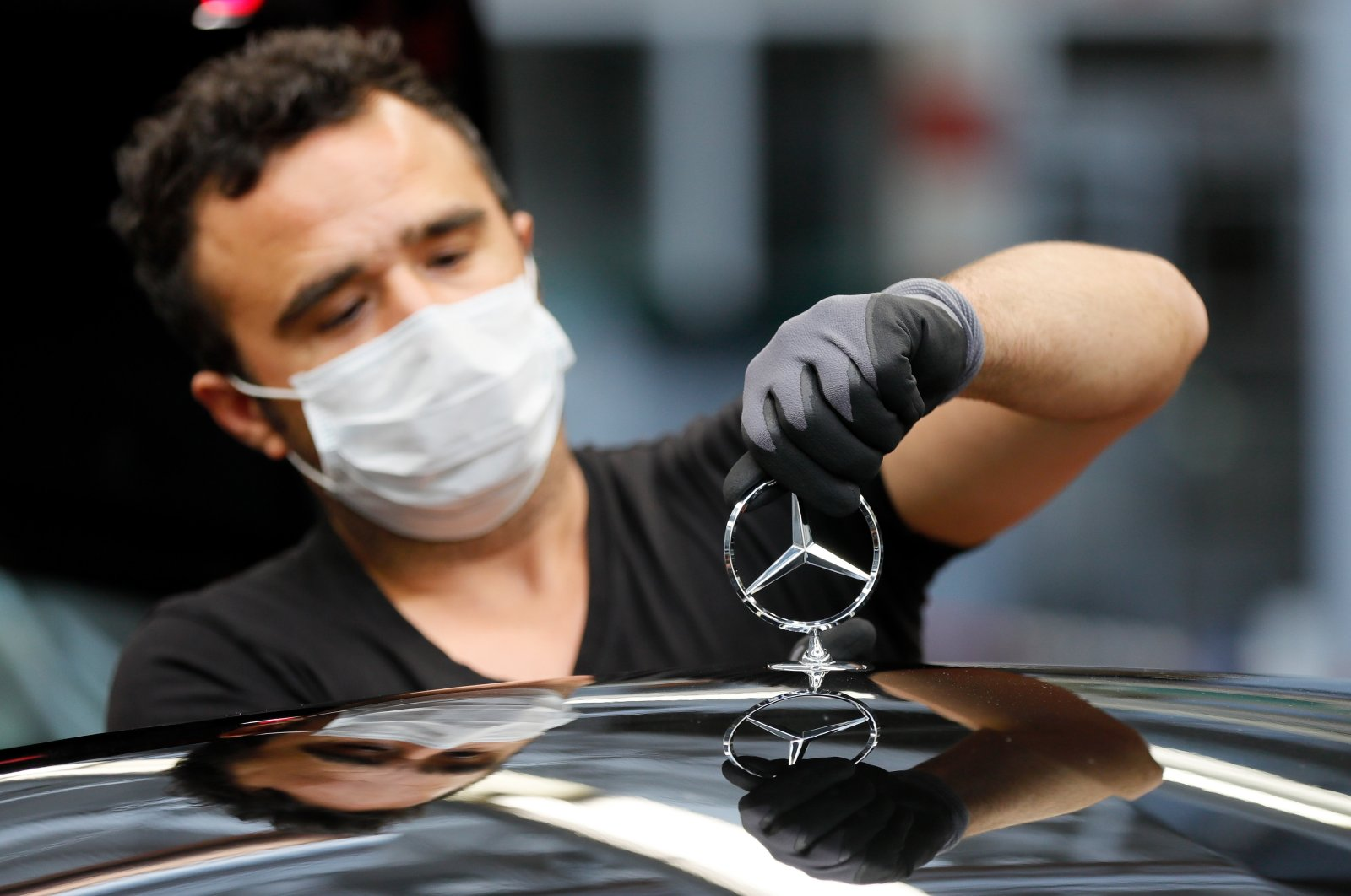 An employee prepares a star on a car at the production of 'S-Class' Mercedes Benz cars at an assembly line during the corona pandemic at the car manufacturer Daimler in Sindelfingen, Germany, April 30, 2020. (EPA Photo)