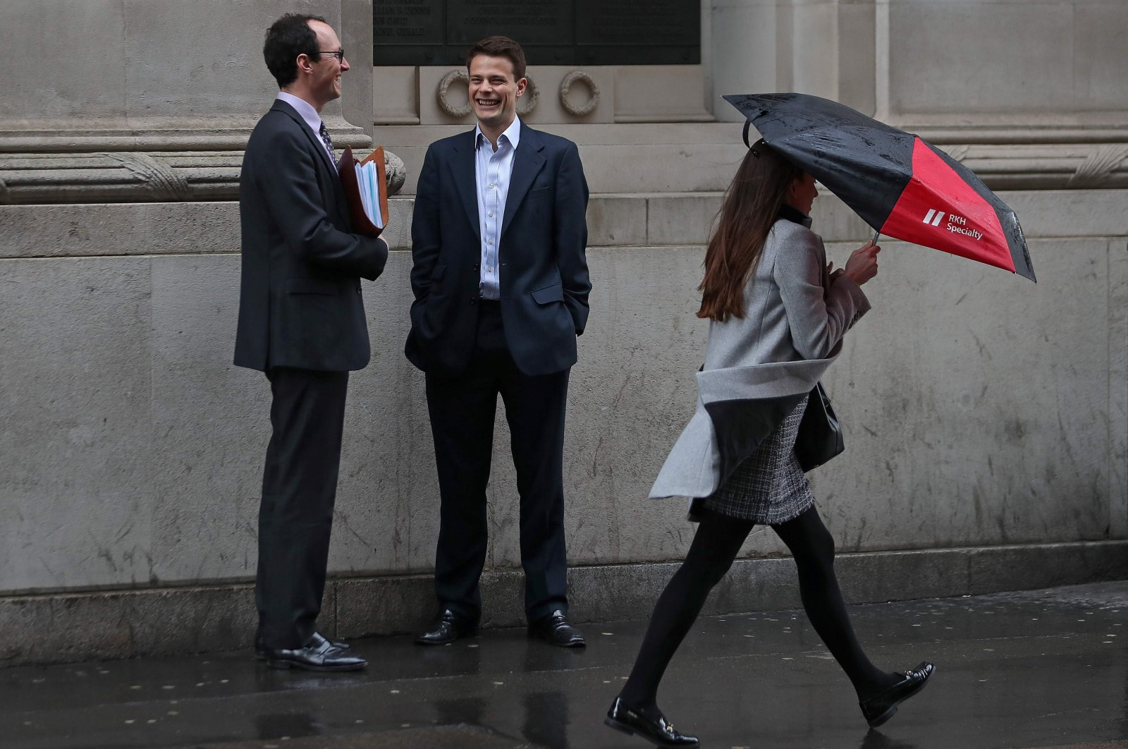 A woman shelters from the rain beneath an umbrella as she walks past talking man in the city of London, U.K., April 4, 2018. (AFP Photo)