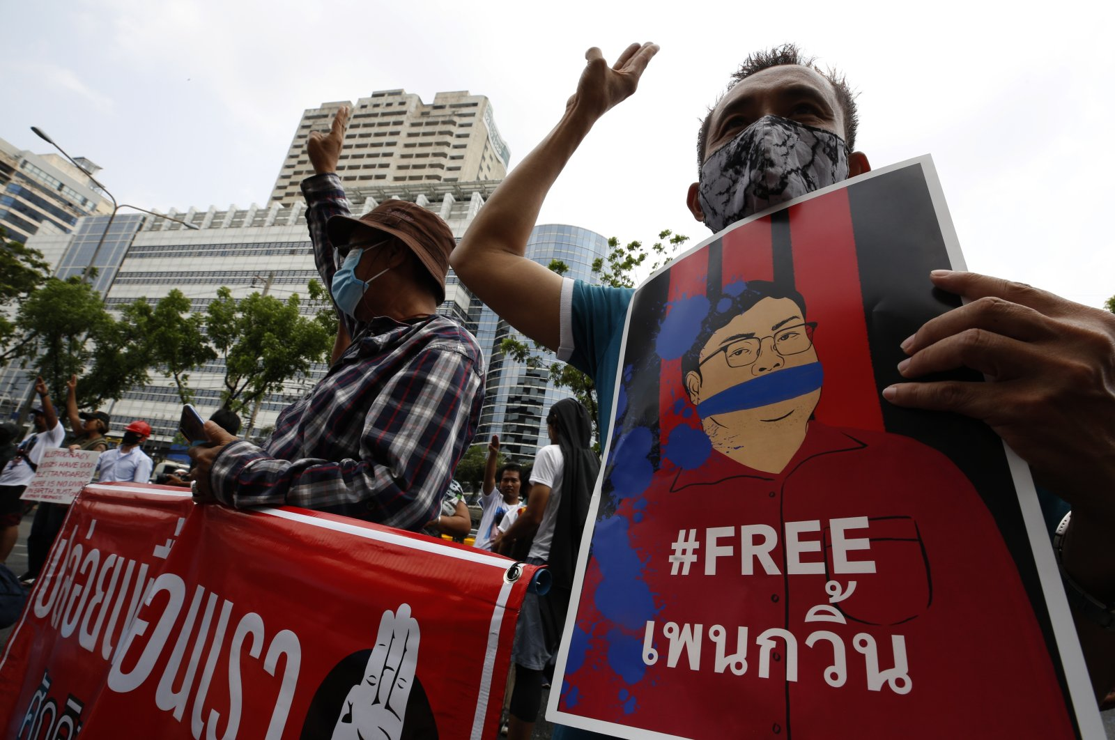 An anti-government protester holds a placard calling for the release of a jailed protest leader Parit Chiwarak as people gather in support of the protest leaders outside the criminal court in Bangkok, Thailand, March 8, 2021. (EPA Photo)
