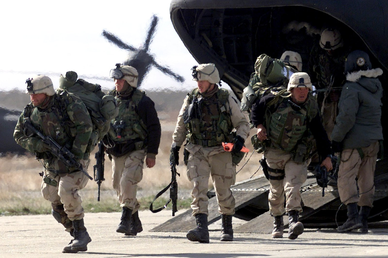 U.S. Army soldiers from the 101 Airborne in full battle gear disembark from a Chinook helicopter as they return to the Bagram base from a week of fighting in the Shahi Kot mountains in eastern Afghanistan, March 11, 2002. (Reuters)