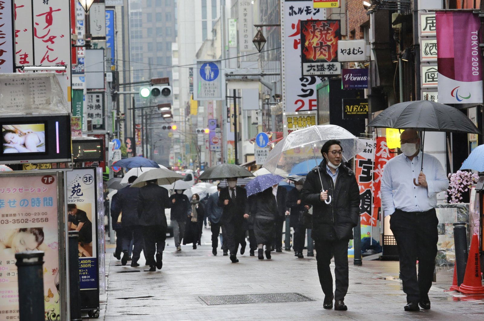 People wearing face masks to protect against the spread of the coronavirus walk on a street lined with bars and restaurants in Tokyo, March 8, 2021. (AP)