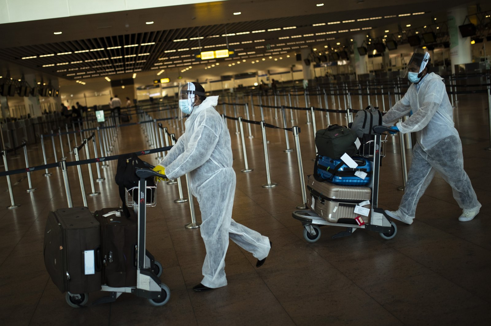 Passengers, wearing full protective gear to protect against the spread of coronavirus, push their luggage to a check-in counter at Zaventem international airport in Brussels, July 29, 2020. (AP Photo)