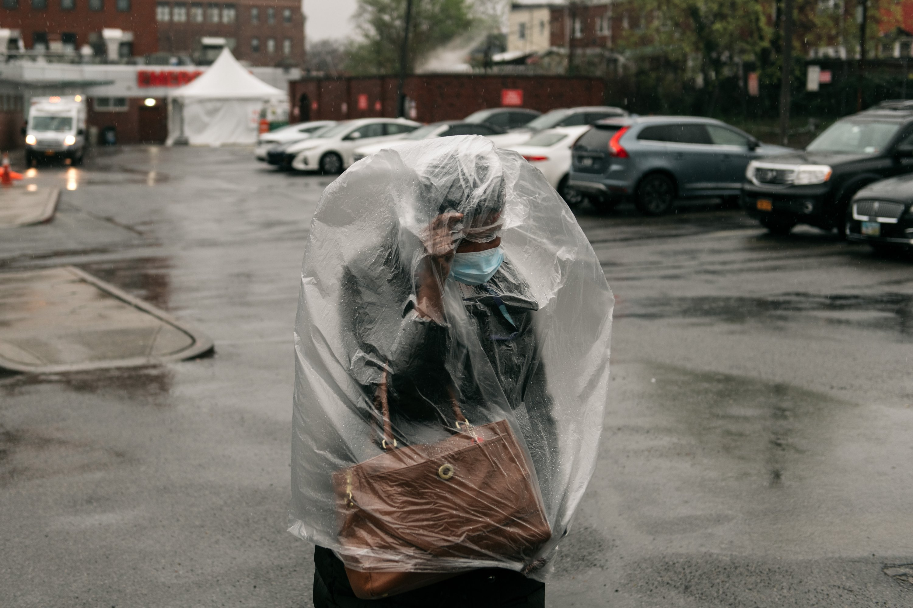 A woman wearing a mask against the coronavirus covers herself with plastic as heavy rain falls in Brooklyn, New York City, U.S., April 13, 2020. (Photo by Getty Images)
