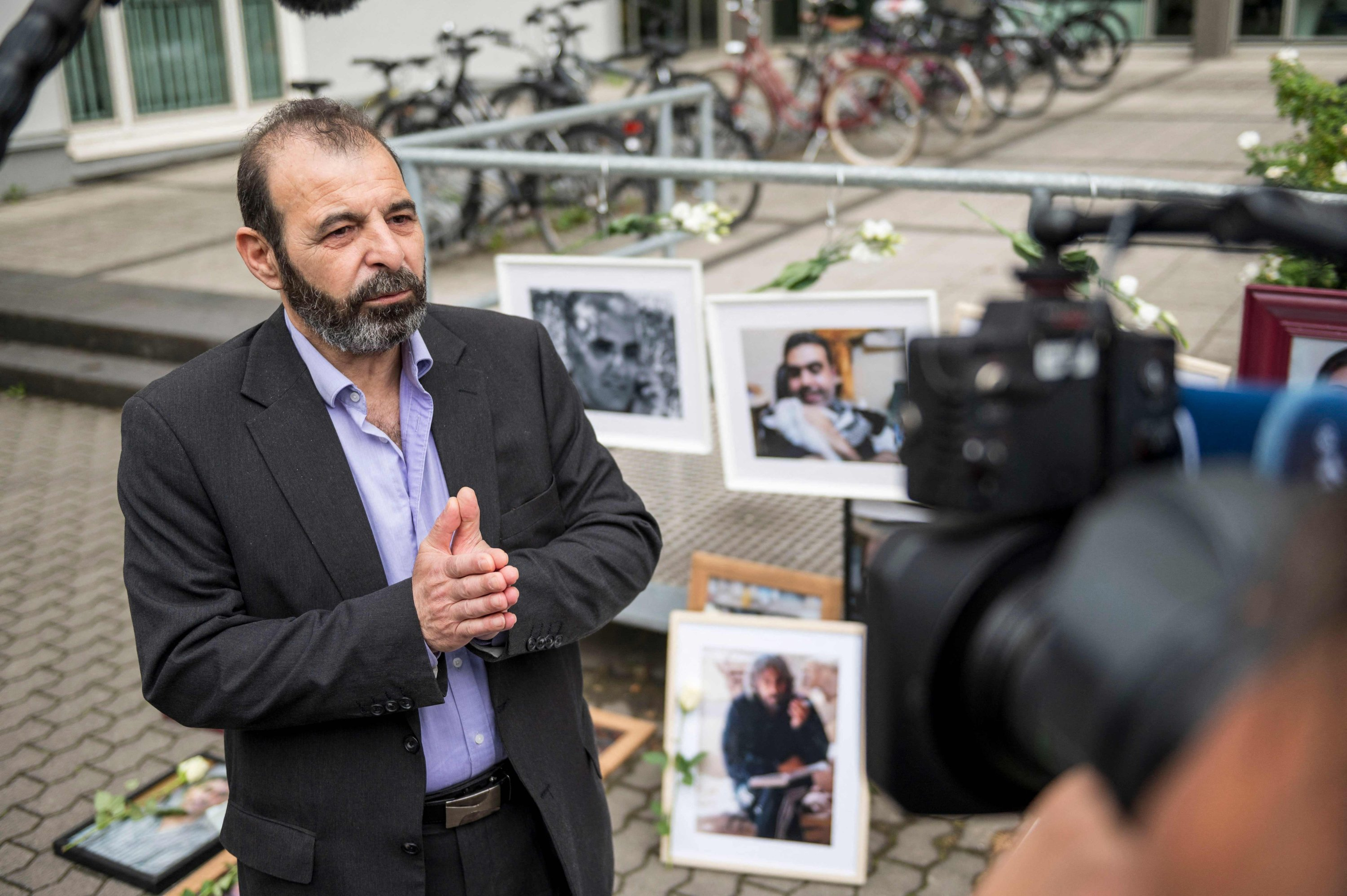 Syrian human rights lawyer Anwar al-Bunni as he speaks to the media in front of pictures of victims of the Syrian regime, during a protest outside the trial against two Syrian alleged former intelligence officers accused of crimes against humanity, in Koblenz, western Germany, June 4, 2020. (AFP)