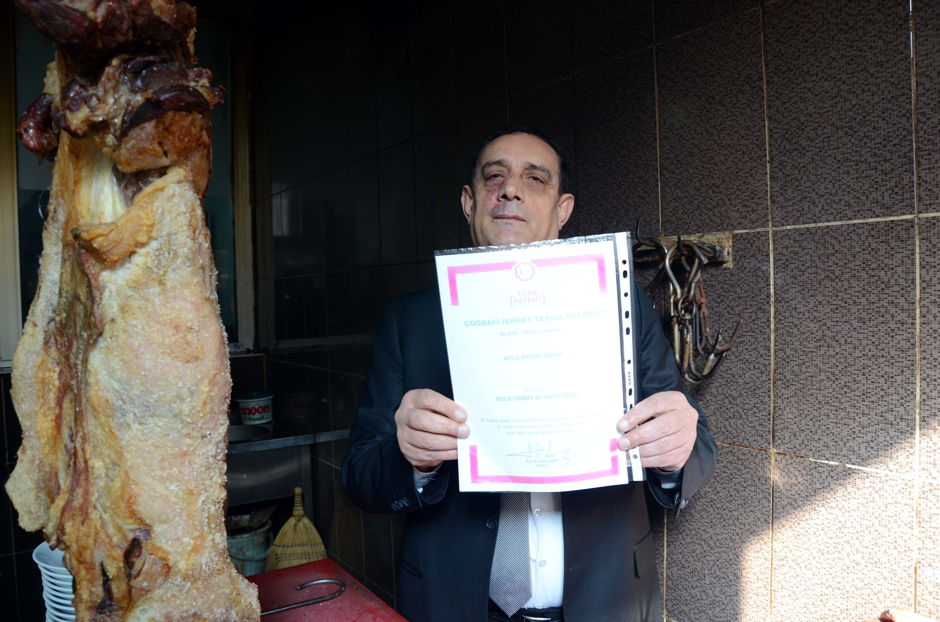 The head of the Bitlis Chamber of Commerce and Industry (TSO) Davut Tezcan poses with the geographical indication certificate of the büryan kebab in Bitlis, southeastern turkey, March 4, 2021. (AA photo)