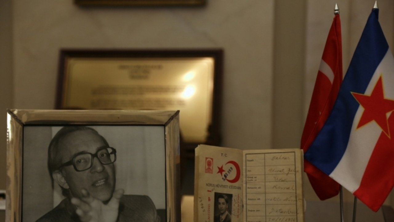 A portrait and the passport of the slain diplomat Galip Balkar are seen next to the flags of Turkey and Yugoslavia in this photo taken at the Turkish Embassy in Serbia's Belgrade on March 9, 2017 (AA File Photo)