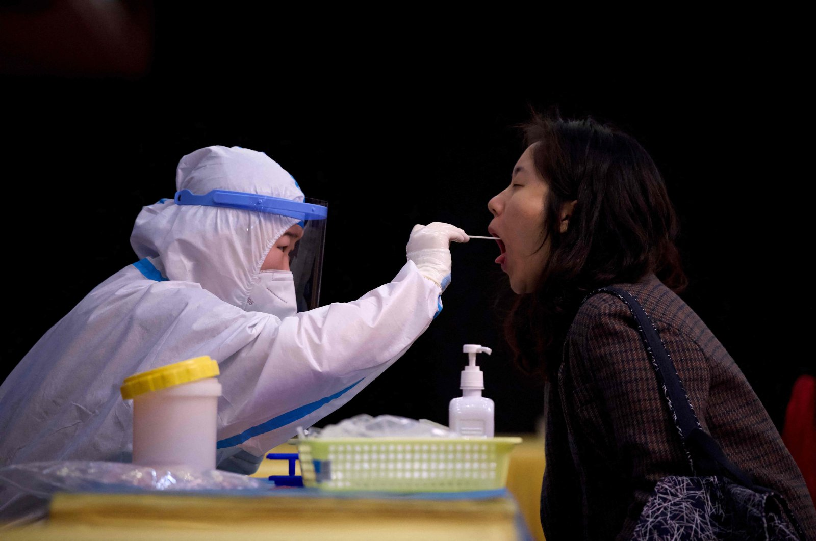 A health worker takes a mouth swab sample from a journalist for Covid-19 nucleic acid tests, nine hours before the second plenary session of the Fourth Session of the 13th National People Congress at the Huabin International hotel in Beijing on March 8, 2021. (AFP Photo)