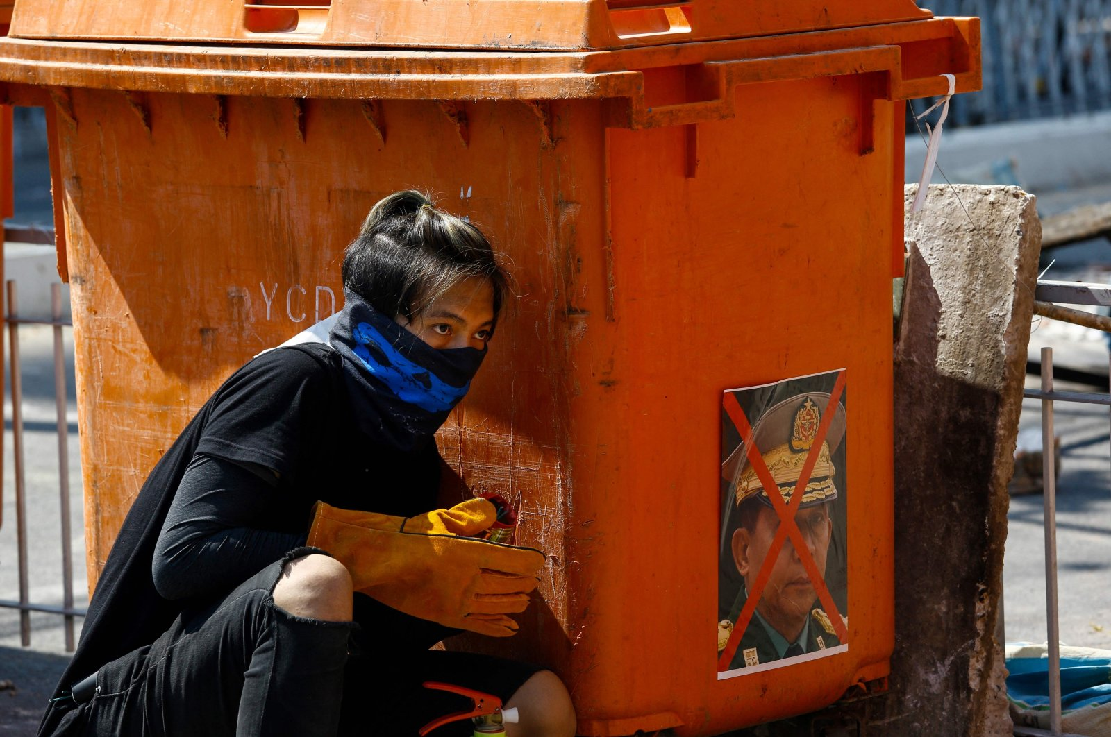 A protester takes shelter behind a rubbish bin adorned with an image of Myanmar armed forces chief Senior General Min Aung Hlaing during a demonstration against the military coup in Yangon, Myanmar, March 8, 2021. (AFP Photo)
