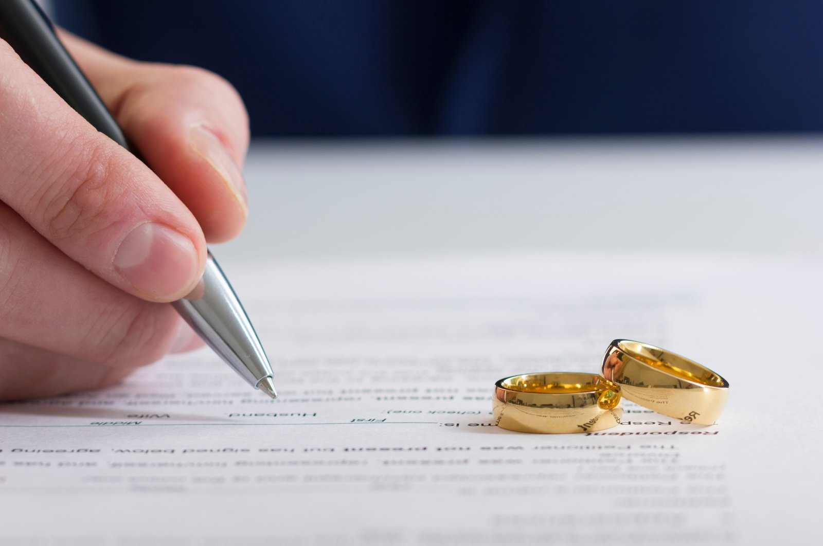 A person signing a document. (Shutterstock Photo)